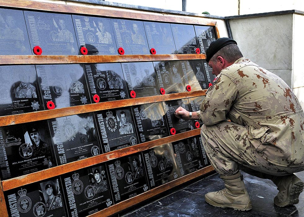 Director of Staff, Strategic Joint Staff, Major-General Jonathan Vance places poppies on every plaque on the Memorial of the Fallen at Kandahar Airfield during the last Remembrance Day ceremony in Southern Afghanistan on November 11, 2011. Photo: Sergeant Lance Wade, Mission Transition Task Force Headquarters. ©2011 DND/MDN Canada.