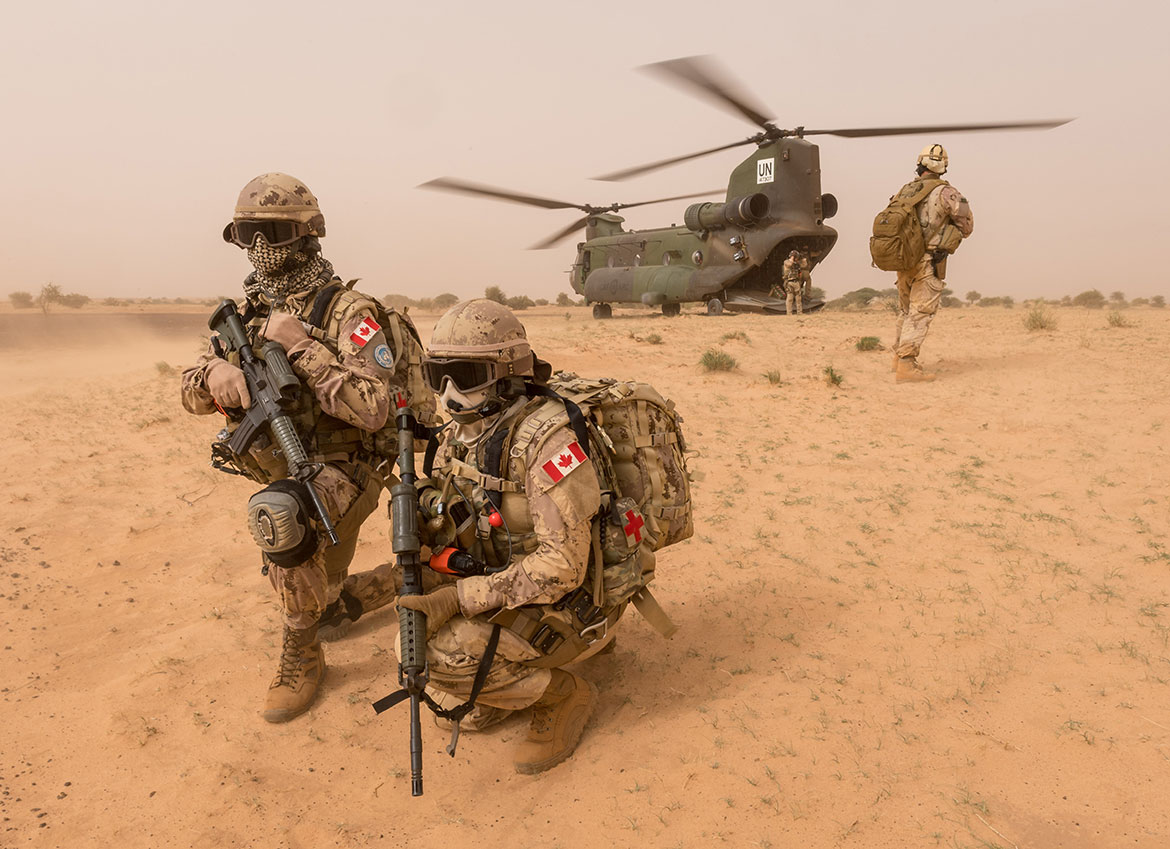 Members of the CH-147 Chinook medical team practice exiting the helicopter under the watchful eye of the force protection team in support of Operation PRESENCE - Mali around Gao, Mali. (Photo: MCpl Jennifer Kusche)