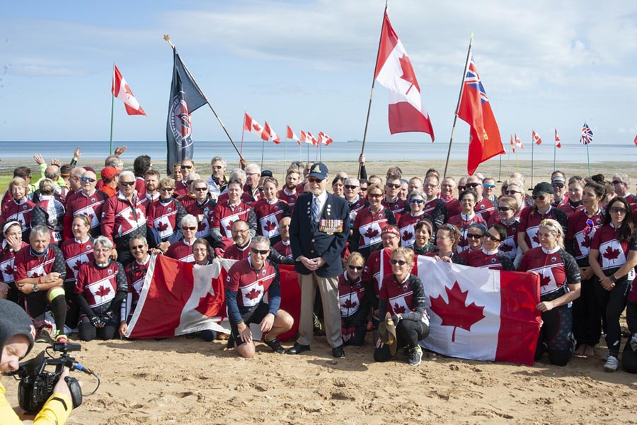 Russell Kaye on Juno Beach, June 6, 2019, surrounded by members of Wounded Warriors Canada's Battlefield Bike Ride 2019 team. It has been 75 years since Mr. Kaye landed on Juno Beach as part of the historic D-Day Landings near Courseulles-sur-Mer, France. Photo: John's Photography, Sooke, BC