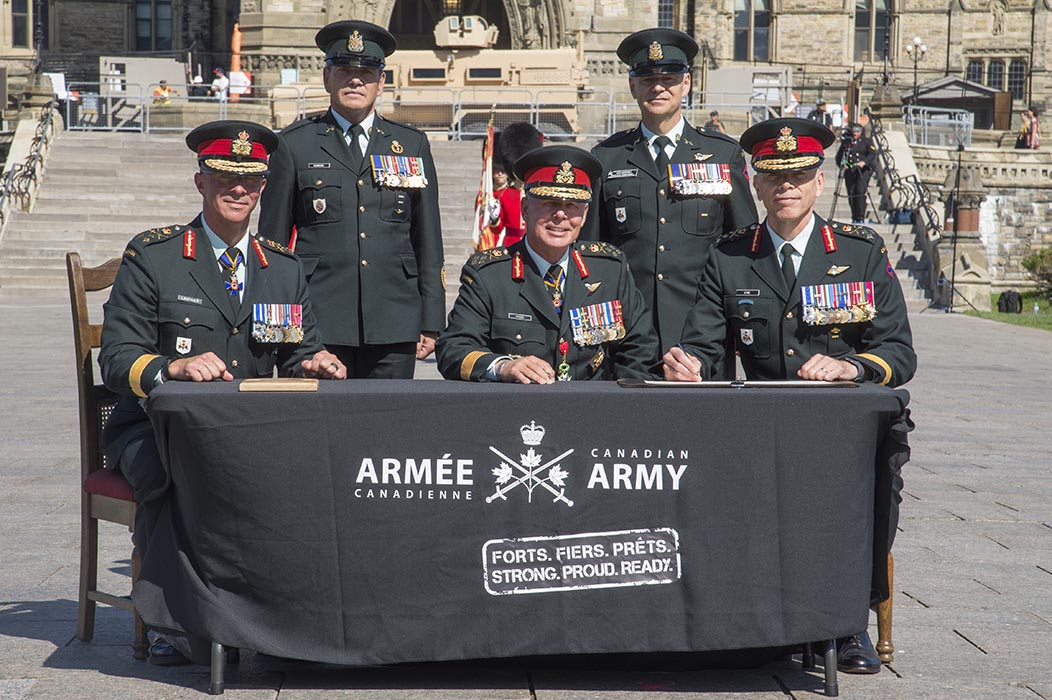 General Johnathan Vance, Chief of the Defense Staff, (centre) Lieutenant-General Jean-Marc Lanthier, outgoing Commander of the Canadian Army, (left) and incoming Commander Lieutenant- General Wayne Eyre (right) sign the ceremonial Change of Army Command scrolls during the Canadian Army Change of Command ceremony at Parliament Hill in Ottawa, Ontario on August 20, 2019. Also pictured are Chief Warrant Officer Alain Guimond, (second left) Canadian Armed Forces Chief Warrant Officer; and Chief Warrant Officer Stuart Hartnell, (second right) Canadian Army Sergeant Major. Photo: Sergeant Lance Wade, 5th Canadian Division. ©2019 DND/MDN Canada.