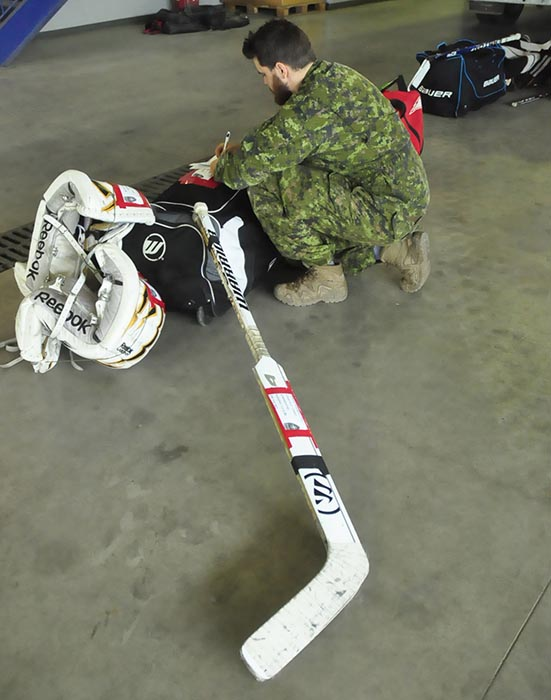 Goalie gear is checked before being loaded on July 8, 2019 at Canadian Forces Base Shilo for the deployment of soldiers on Operation REASSURANCE in Latvia. Cultural exchange in the form of hockey builds bonds of friendship between Allied countries. Photo: Jules Xavier, Shilo Stag newspaper.