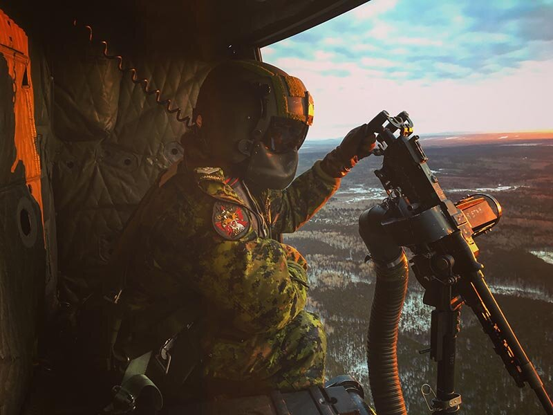 Sergeant Brigitte O'Driscoll on board a CH-146 Griffon helicopter flying over the 5 Canadian Division Support Base Gagetown training area after a shooting exercise. Sgt O'Driscoll, an Army Reservist from Montreal, is just the second female Canadian soldier to become a Door Gunner. Photo: Provided by Sergeant Brigitte O'Driscoll.