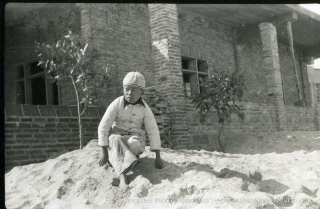 Chinese boy on dirt pile.jpg