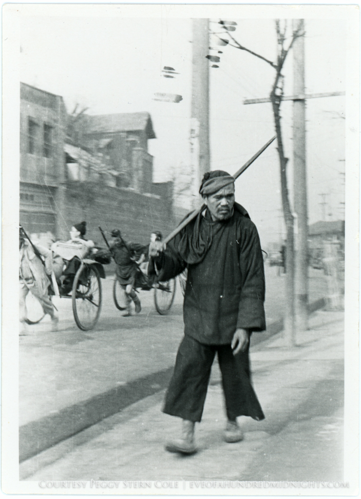 Man WIth Stick Walking in Front of Rickshaws [From White Bordered Print].jpg