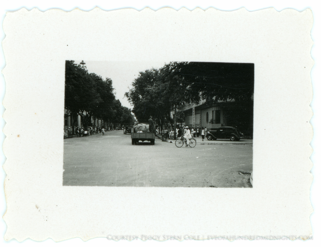Truck of Japanese soldiers on Hanoi corner with bicyclist.jpg