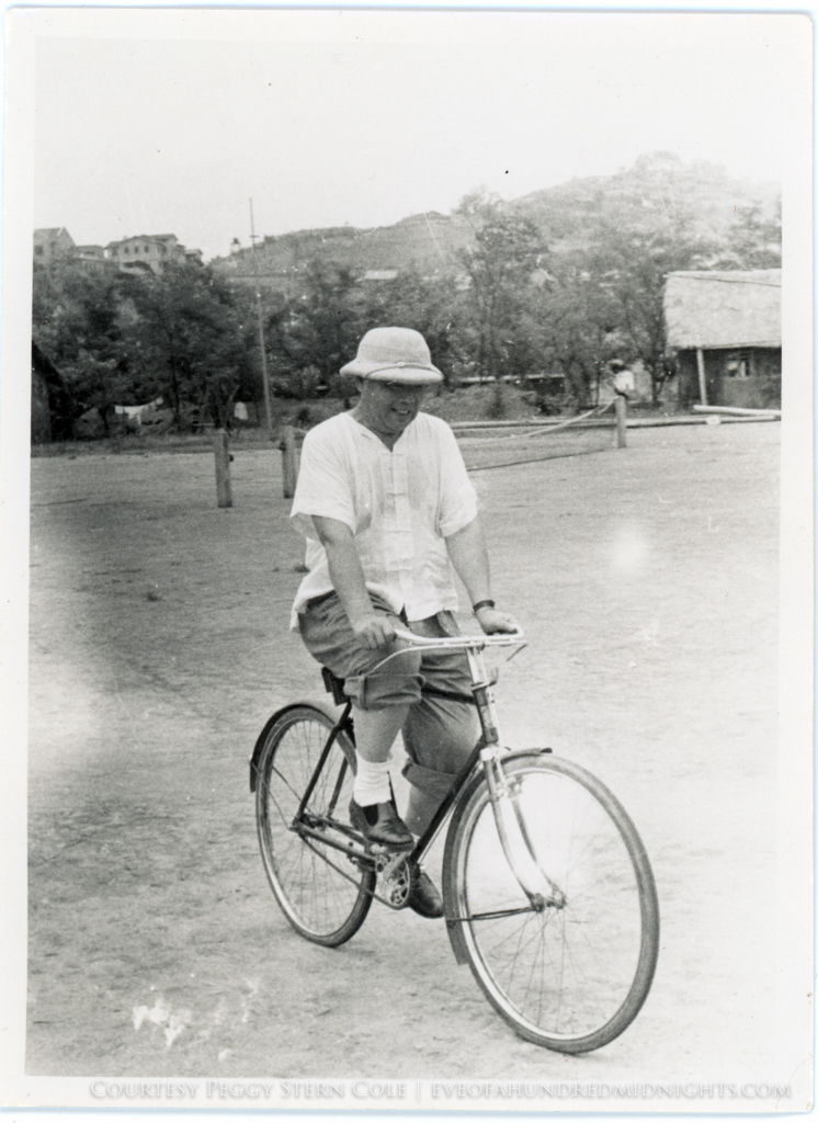 Man in pith helmet riding bike on tennis court [possibly chungking press hostel].jpg