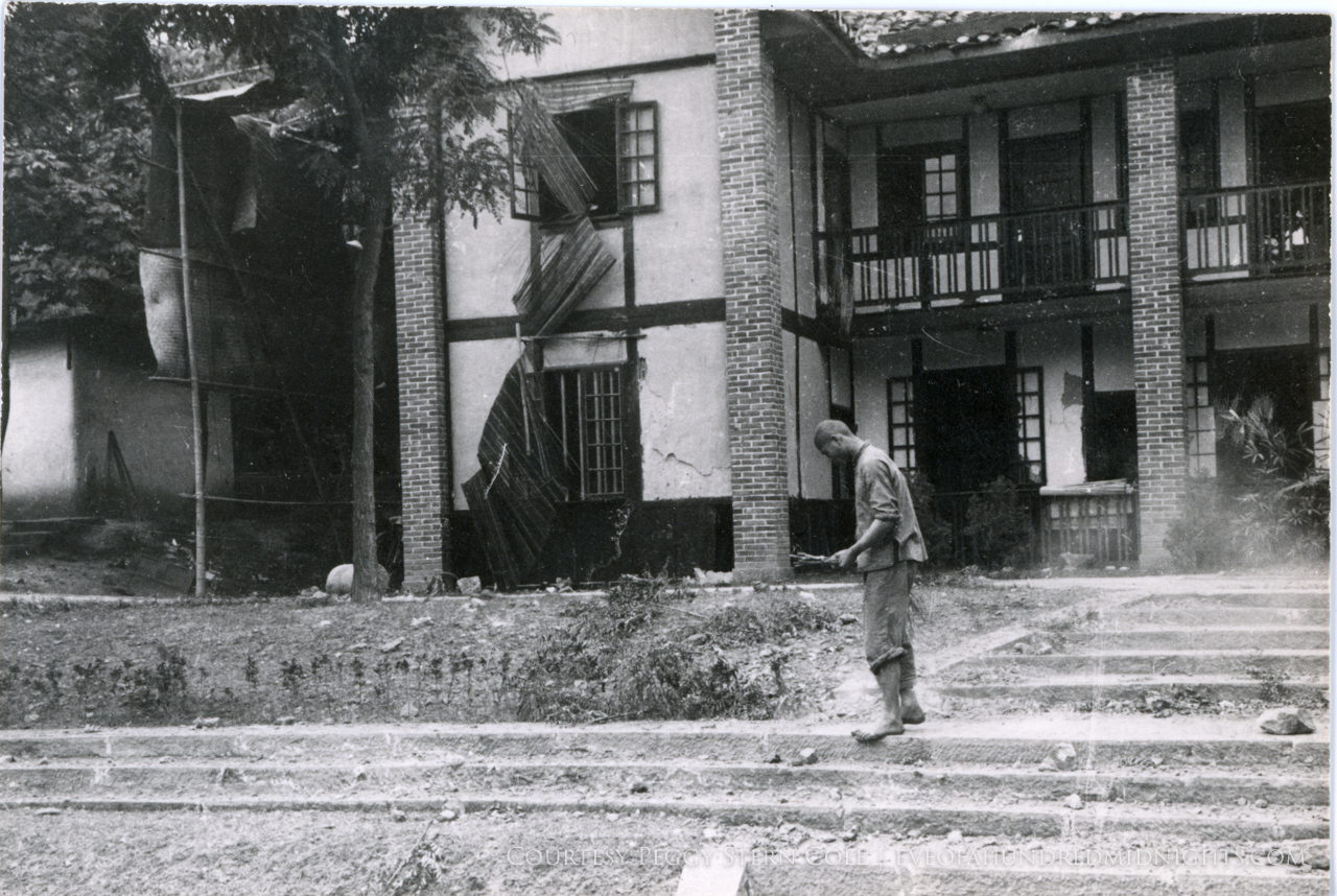 Press Hostel Damaged Windows and man walking with sticks in front.jpg