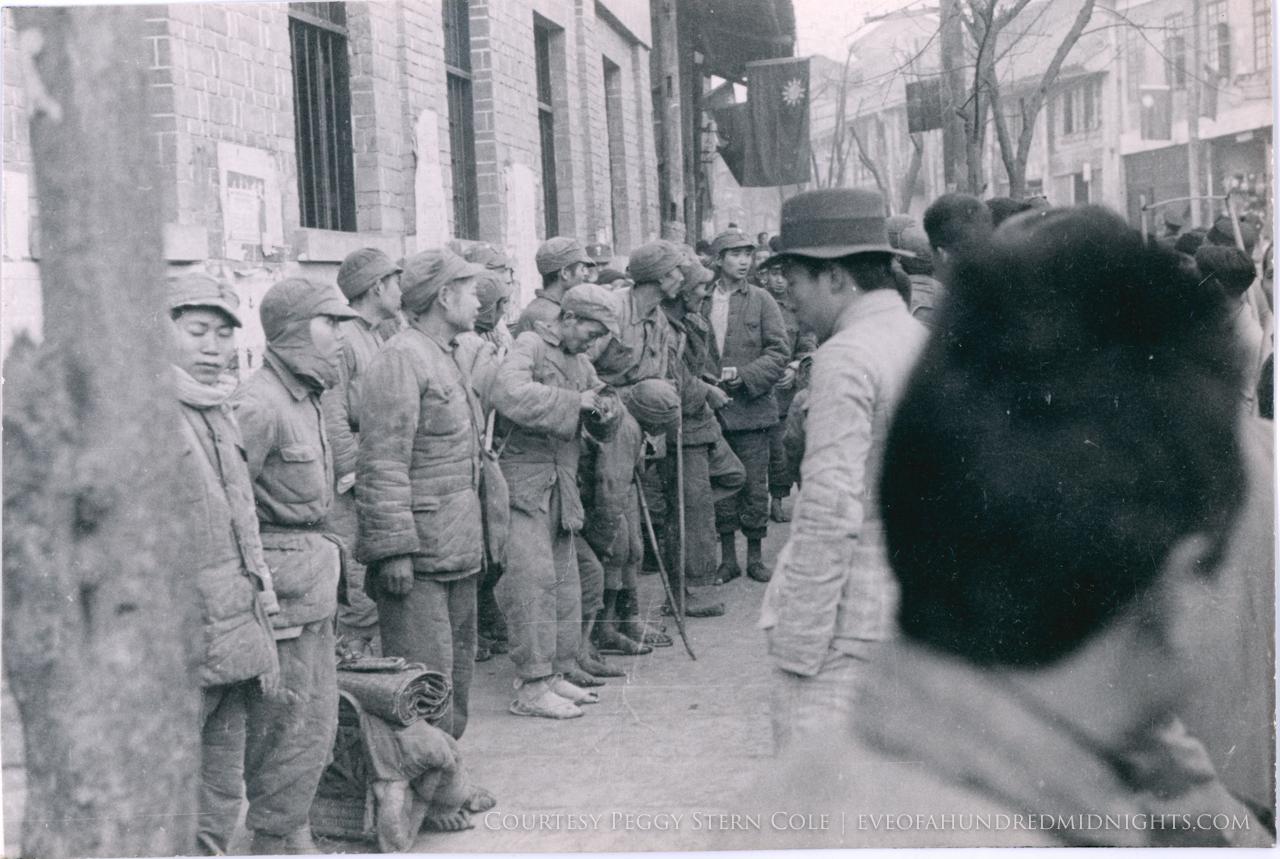 Men in workclothes in line on sidewalk.jpg