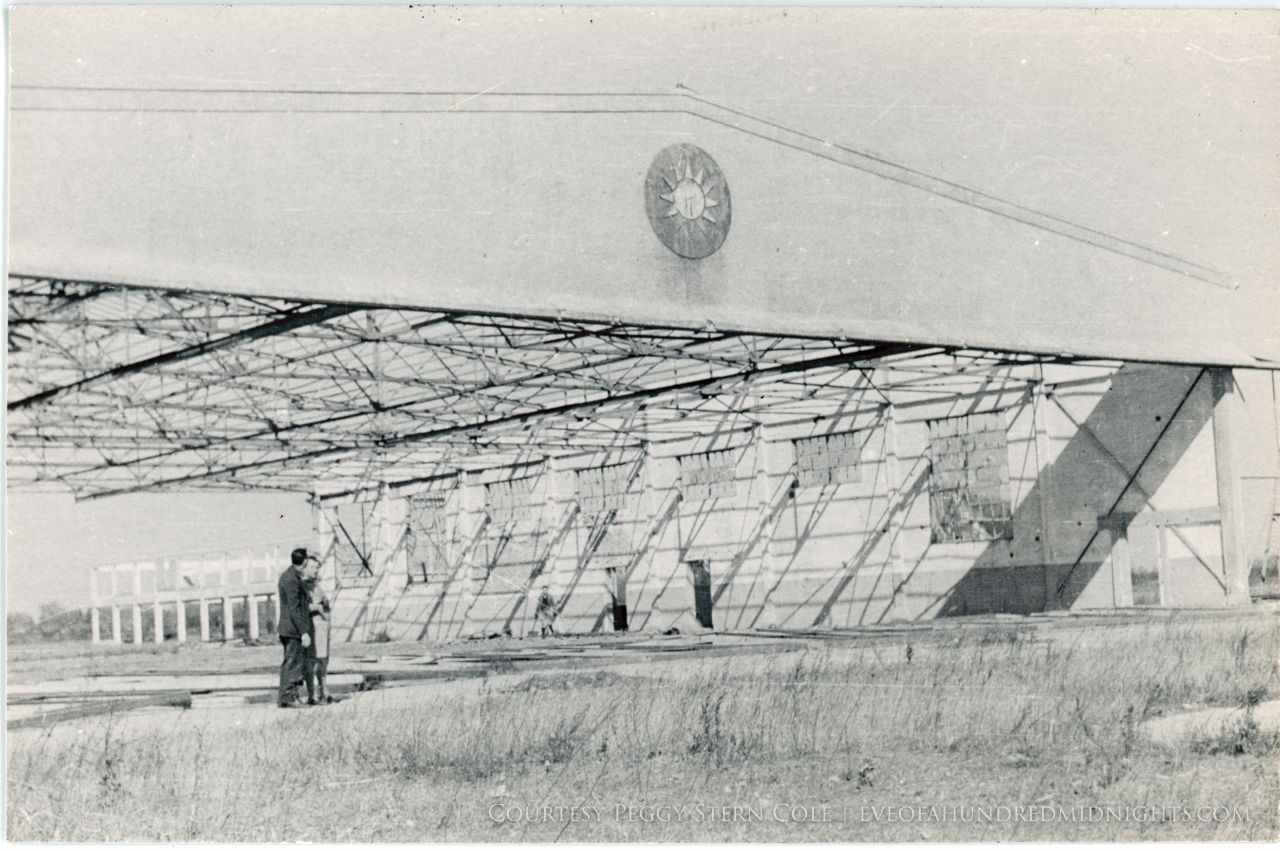 Abandoned RoC hangar with two people in front.jpg