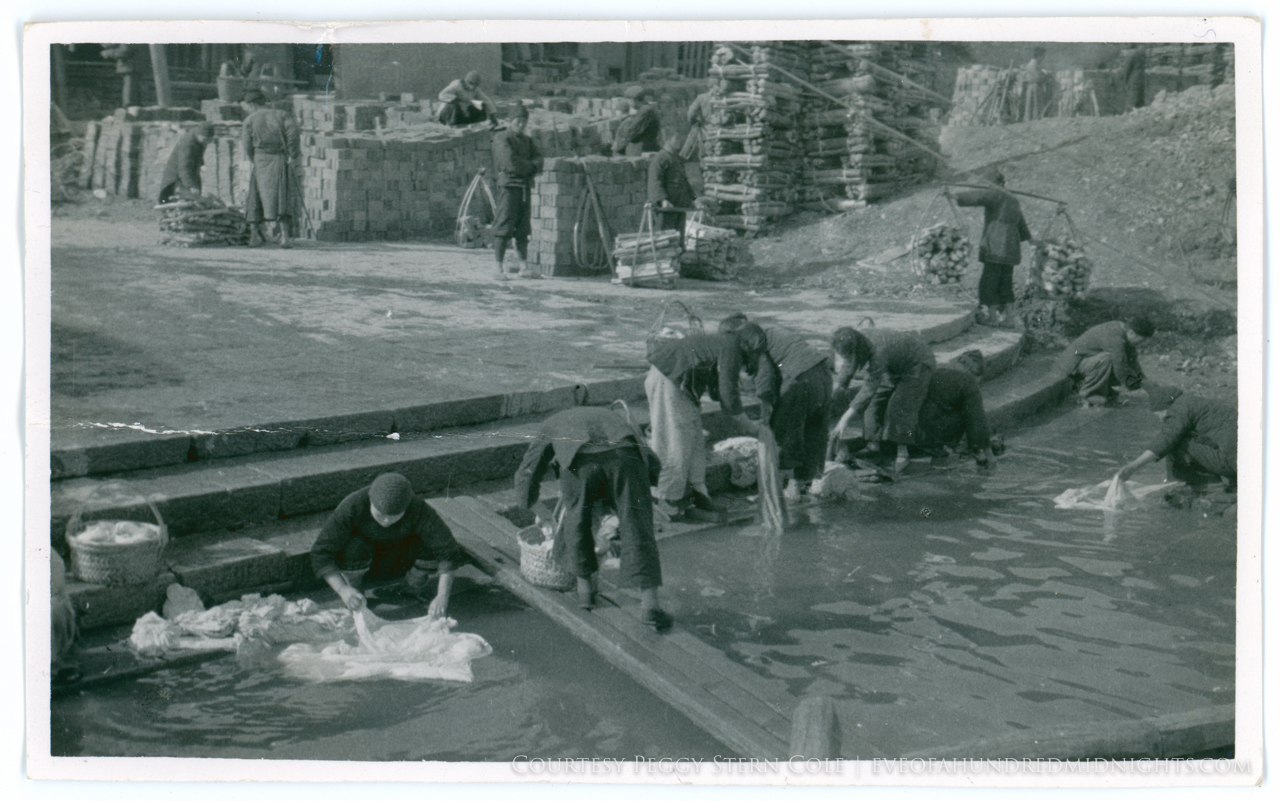 People doing washing in river near brick piles.jpg