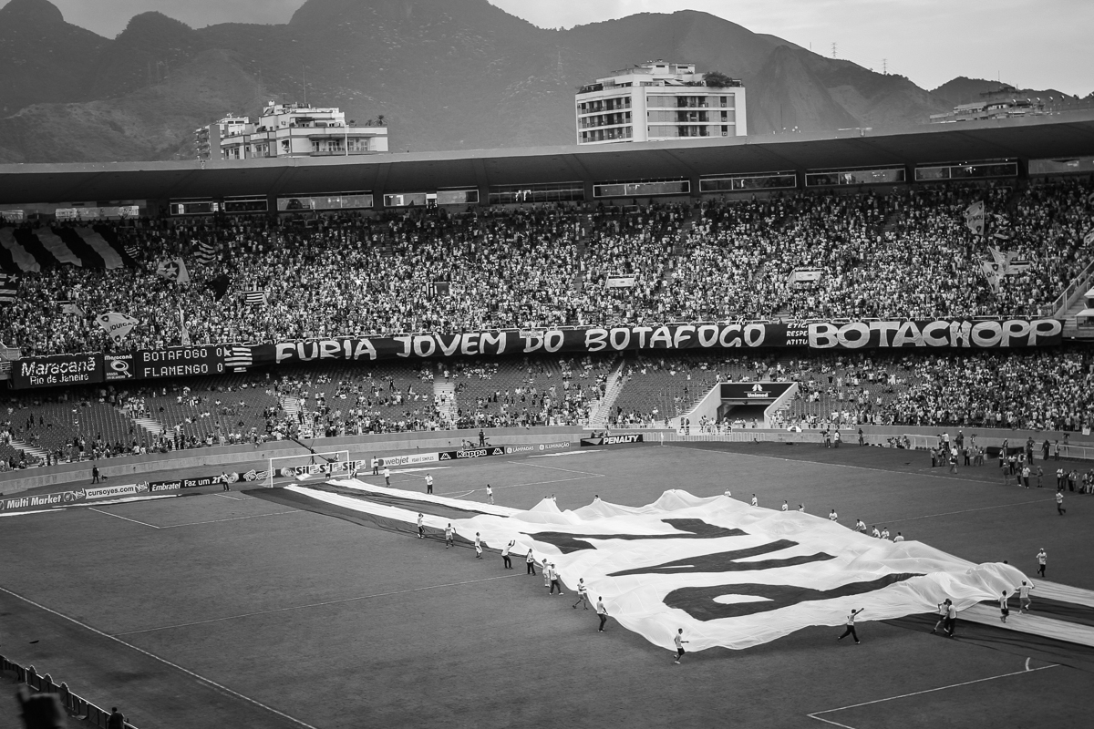 """Before the game starts a big banner saying """"Peace"""", is brought to the center of the field along with banners with the colors of the two teams."""