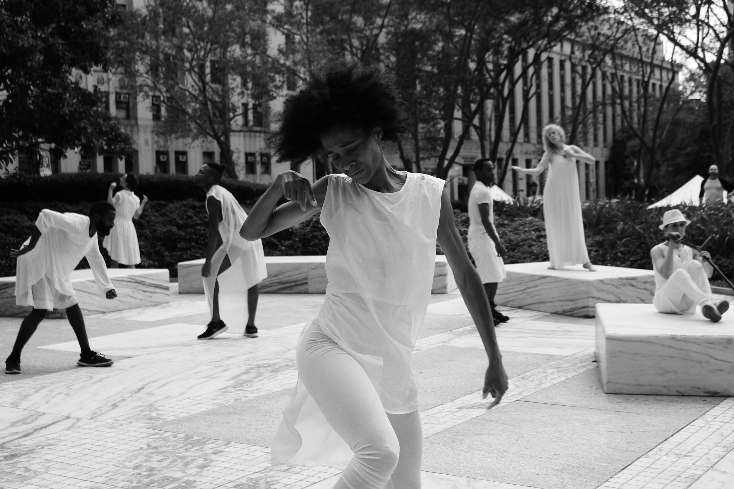 a group of dancers in white in an open courtyard as sculptures