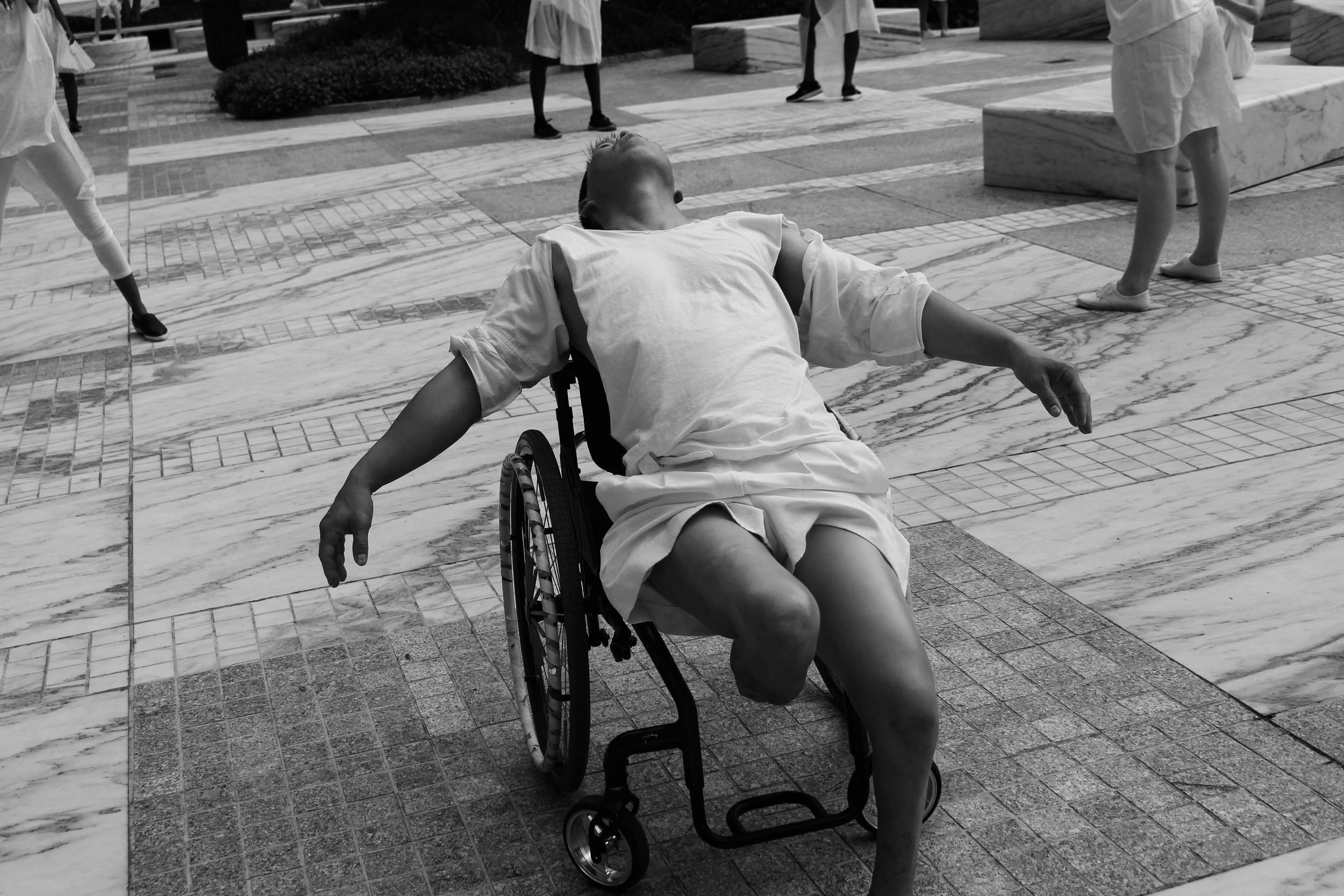 black and white photo: a man sitting back in his wheelchair, he is missing two legs, his head is back and his arms outstretched