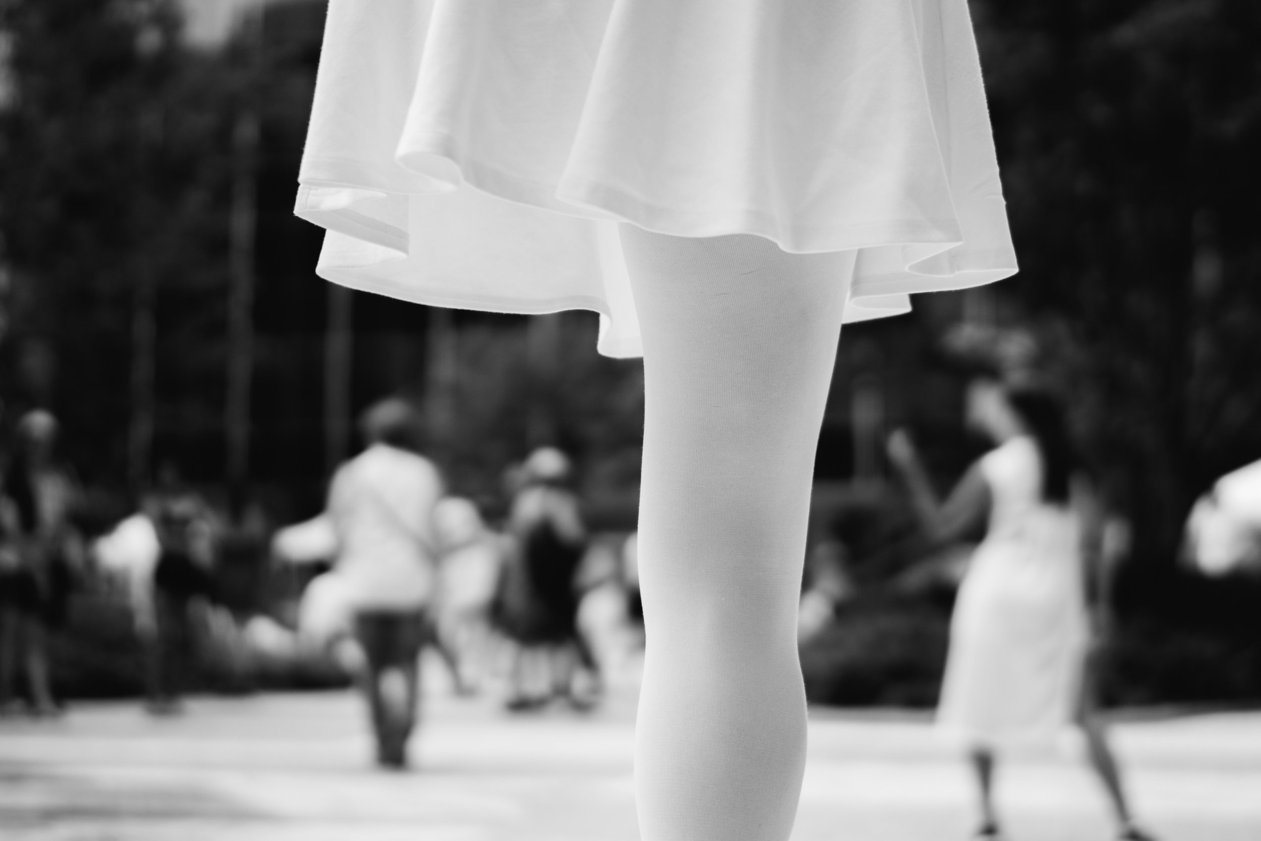 black and white photo of a woman in a white skirt with one leg