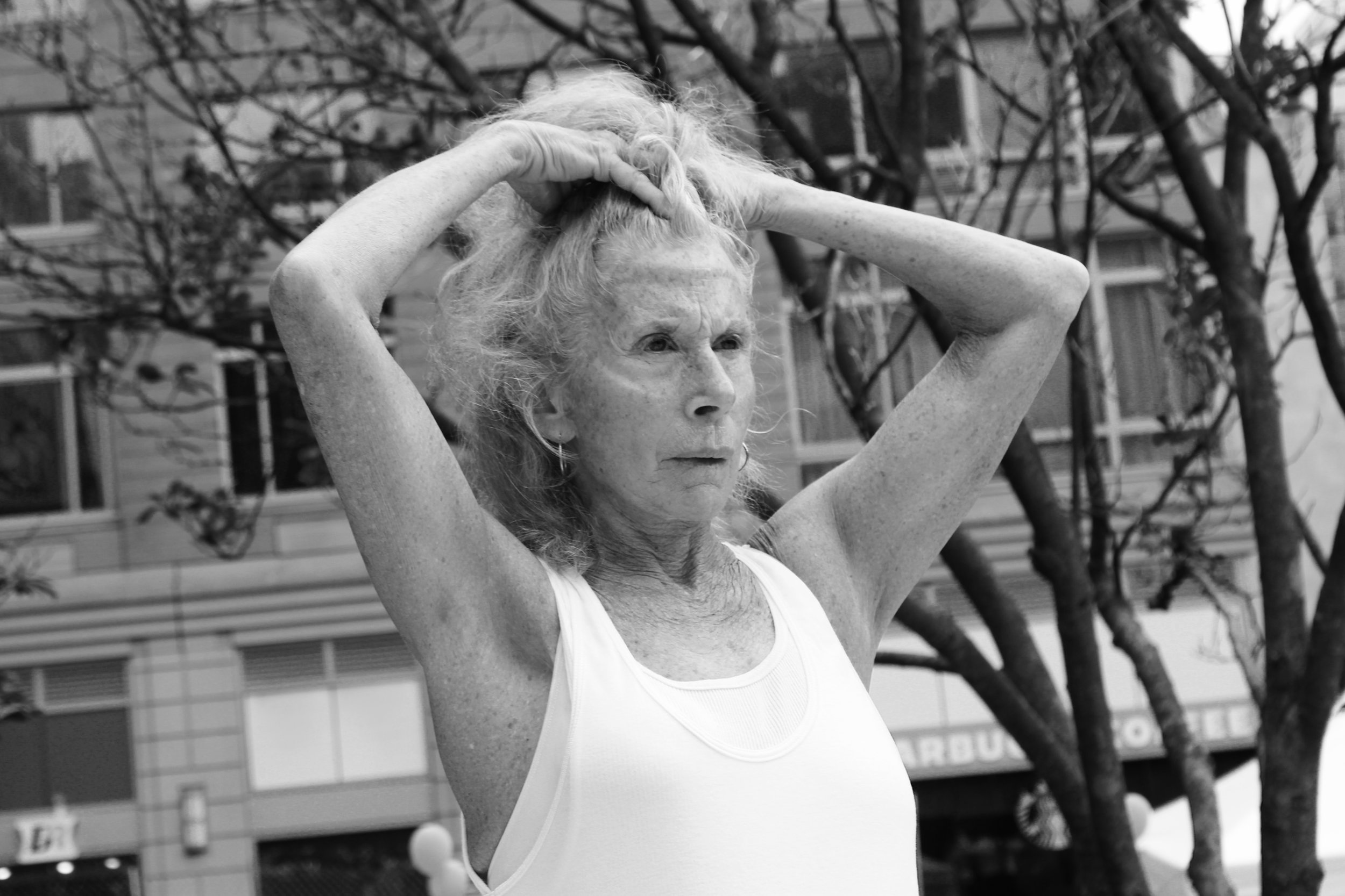 black and white photo of an older white woman looking out with hands in her hair