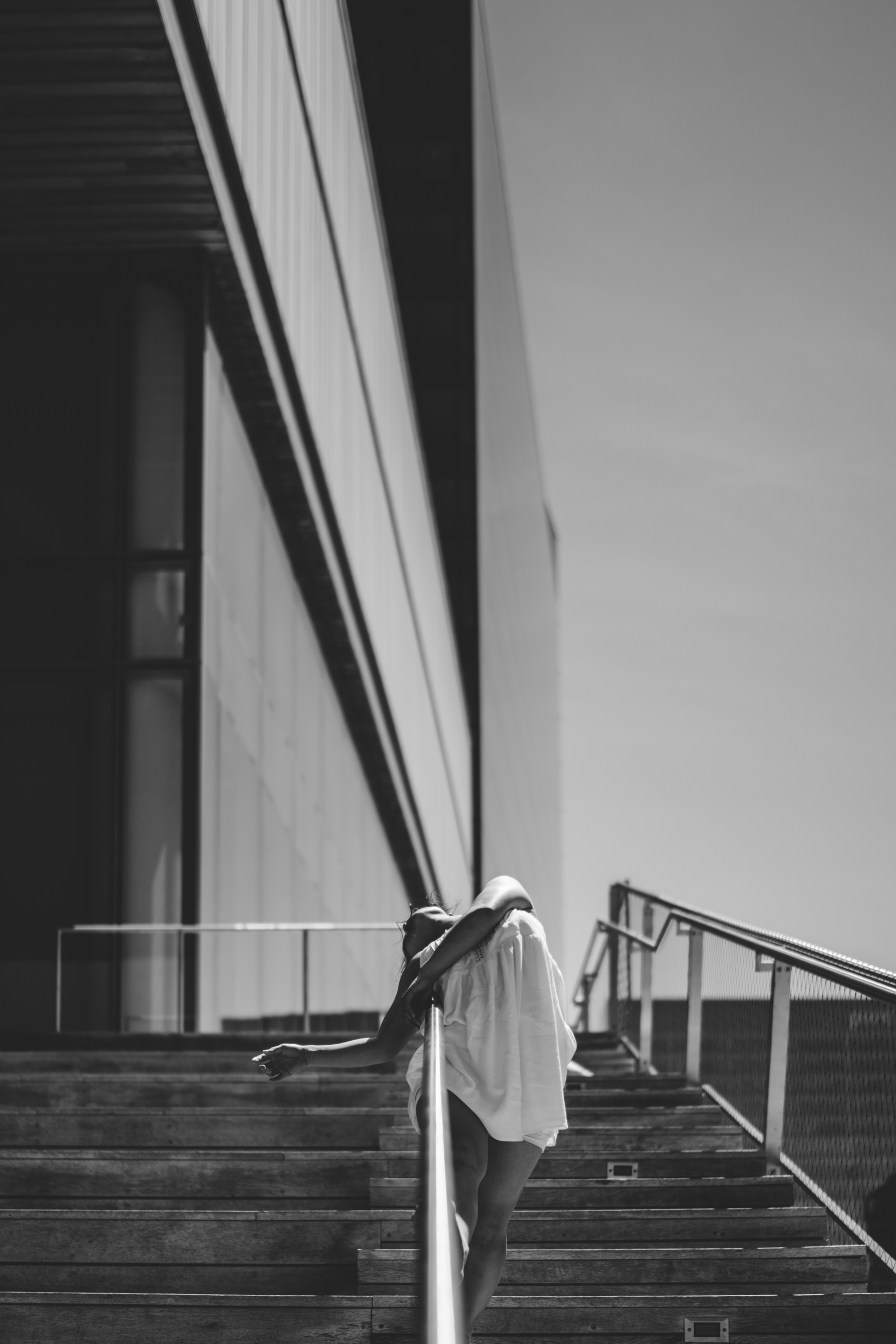 black and white photo: a woman drapes over a outdoor railing