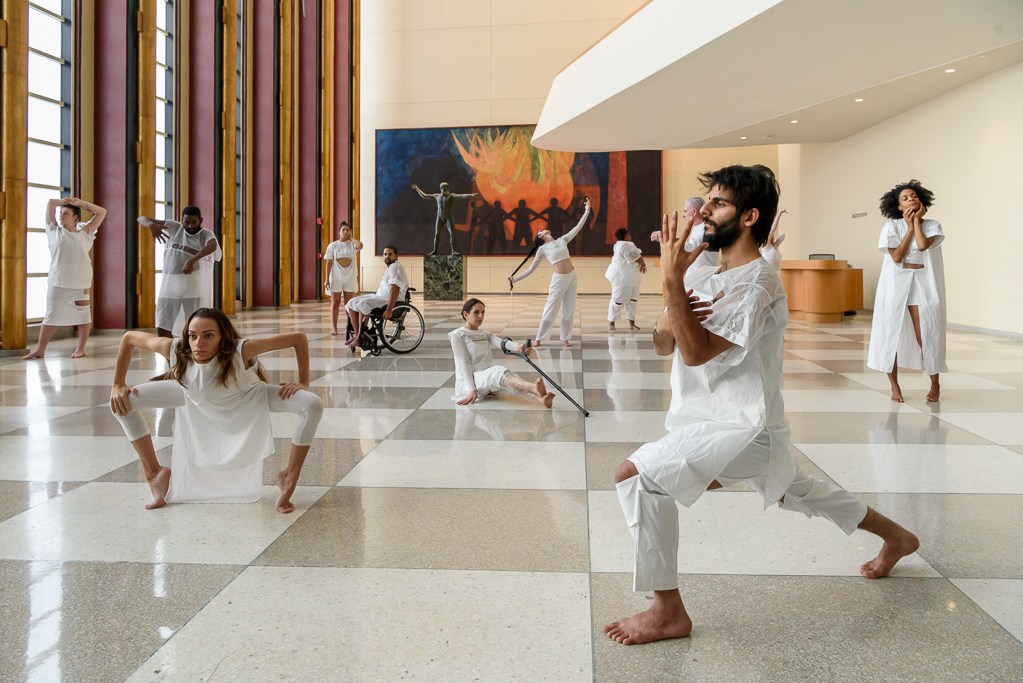color photo: a group of performers in white like statues in the lobby of the United Nations
