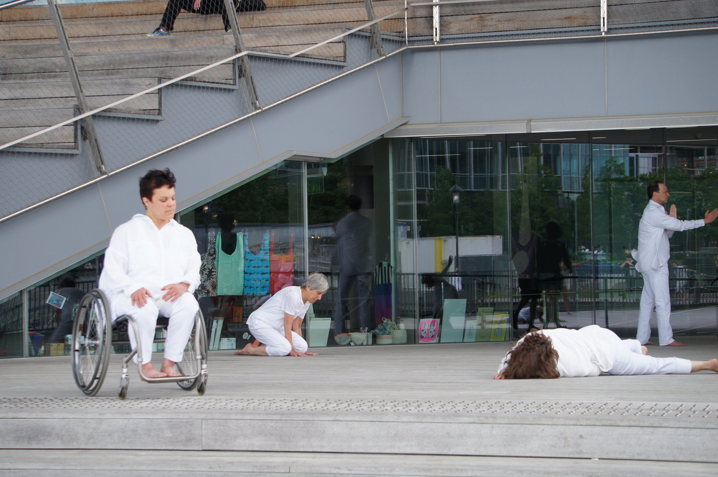 color photo of a group dressed in white on a deck; woman sits in a wheelchair with eyes closed; a woman lays headfirst on the ground; an older woman kneels looking out; a man stretches out his arms
