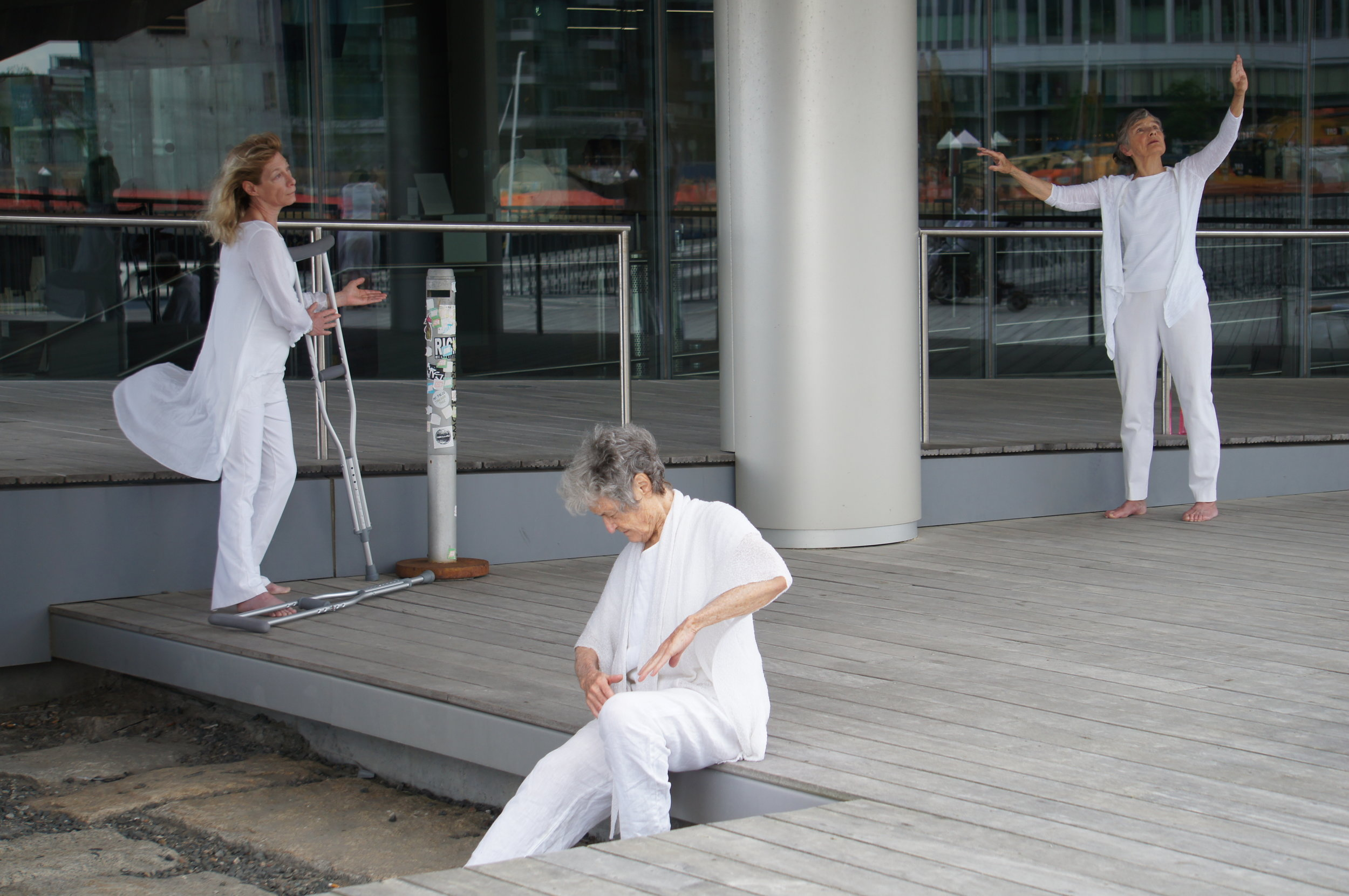 color photo of three older women underneath an incline, dressed in white, one holding herself and sitting, one with outstretched arms, the other looking out