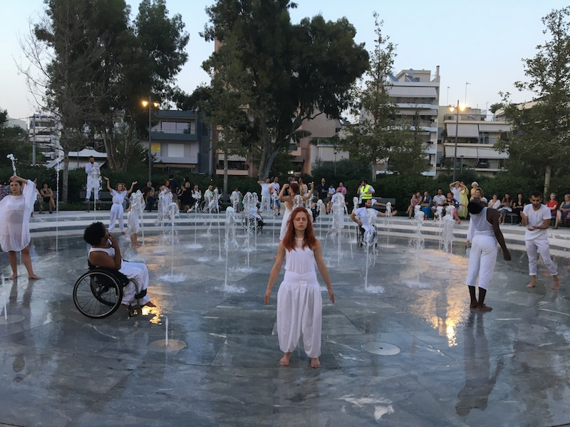 color photo of a sculpture court filled with people in white, standing in various poses around a fountain shooting up water.