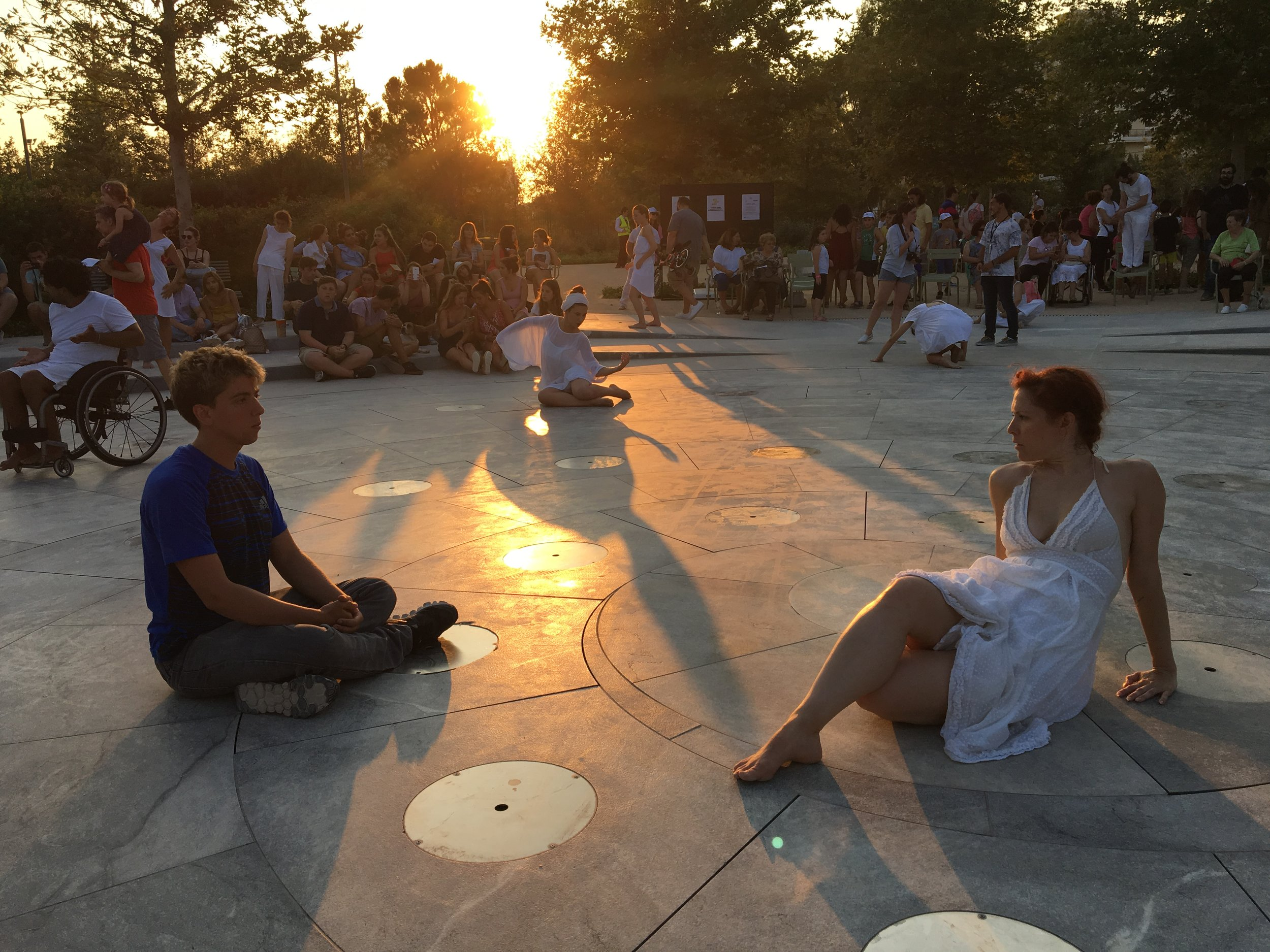color photo of a man sitting on the ground in front of a woman also sitting, dressed in white, holding a pose. A ray from the sunset splits through the photo.