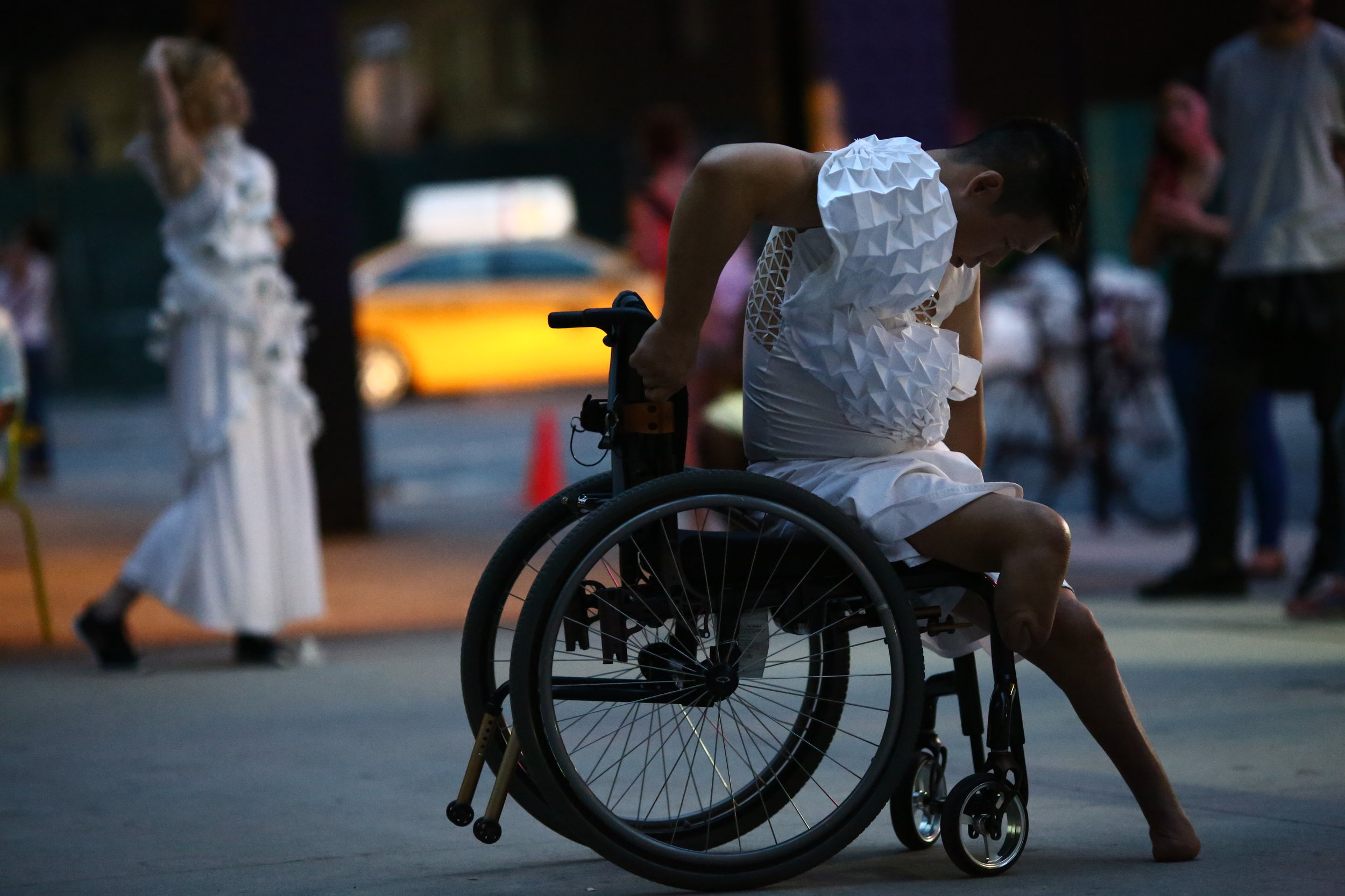 color photo of man sitting in his wheelchair wearing an embellished white shirt, extending his left leg onto the ground, looking down