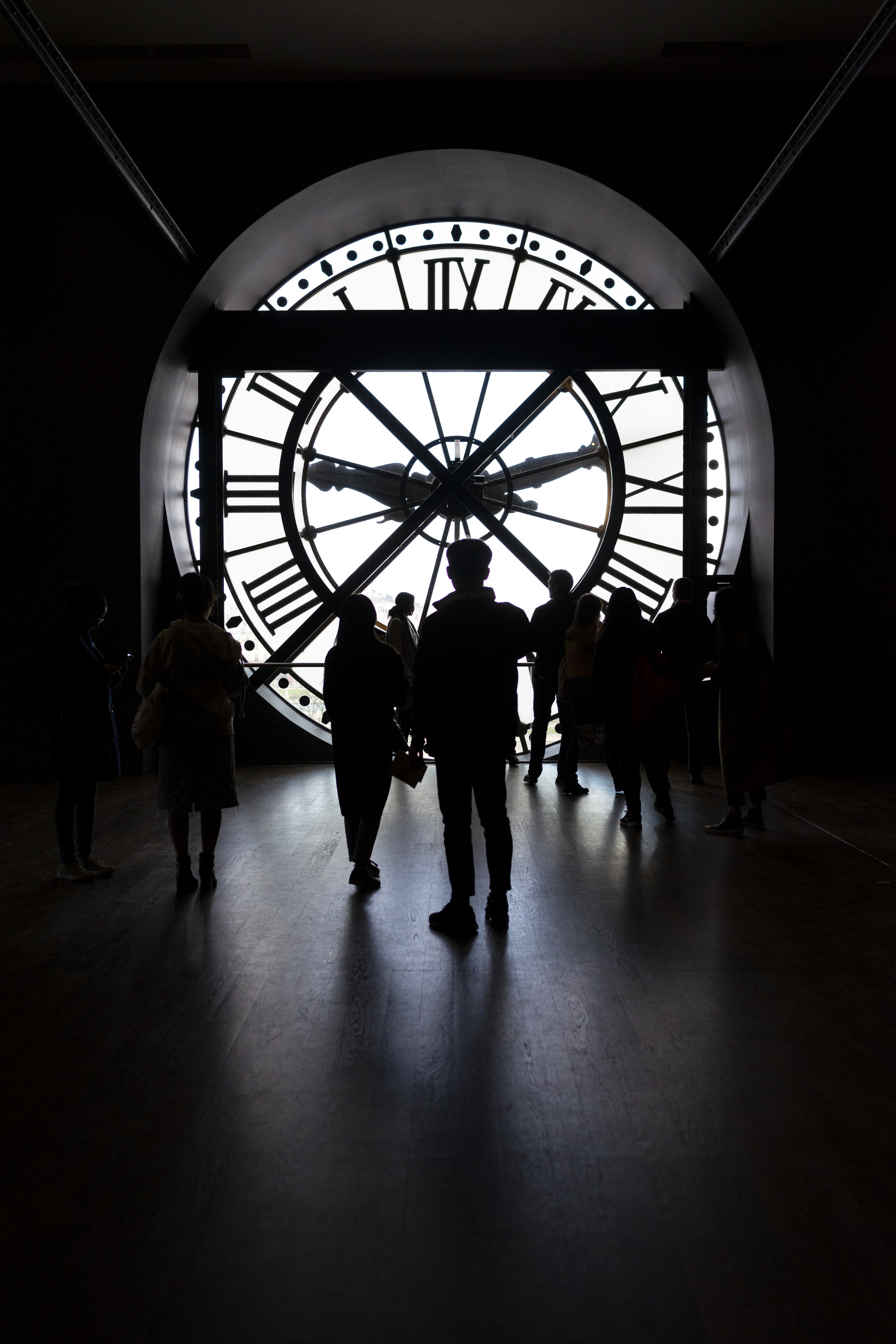 A group of visitors at the Musée d'Orsay are silhouetted as they look through the clock face to see the city of Paris. (Elise Marie Photography)