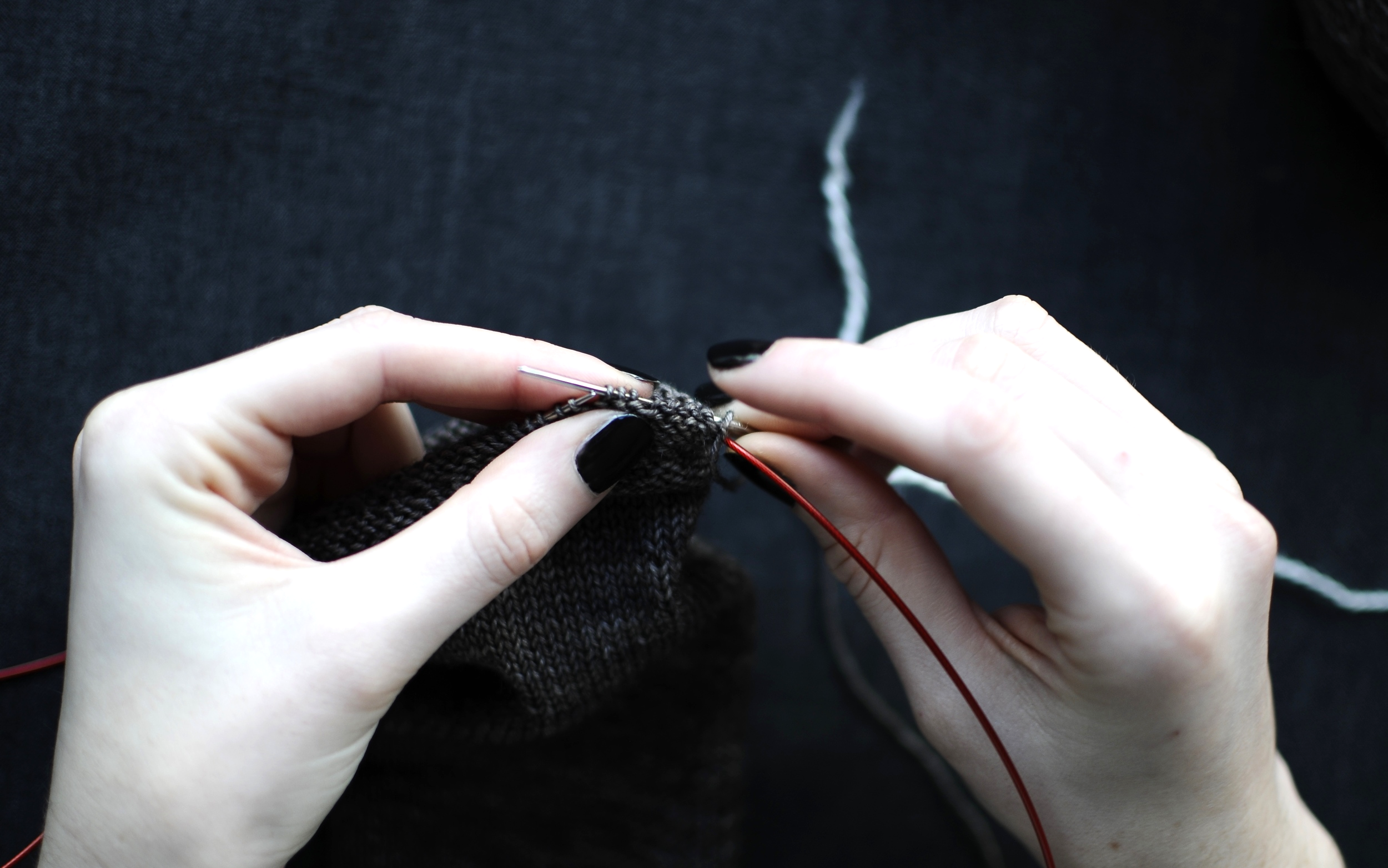 1. Break Yarn A and leave a long tail,approximately three times the circumference of your sock, for sewing down the picot hem.Thread the darning needle with Yarn B. Slowly thread the stitches from your needle onto the darning needle and Yarn B. Work in a clockwise direction.