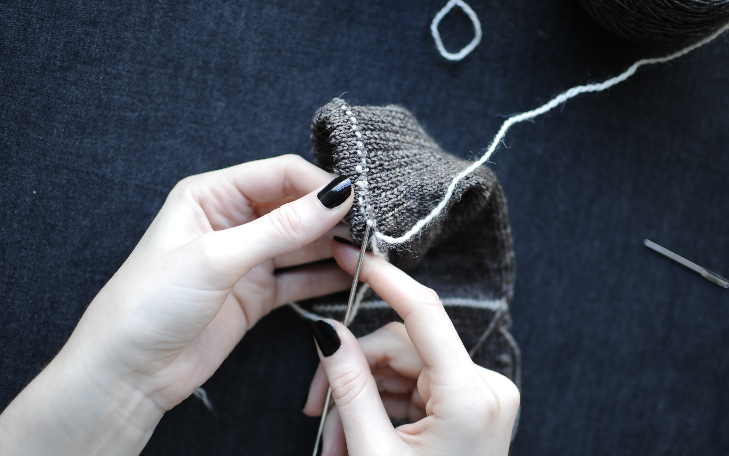 2. Start at the seam where you left Yarn B. Pick up the working yarn and begin to work in an anticlockwise direction. Insert the needle under Yarn B, as if to knit (in-between the stitches you used to sew down the picot hem).