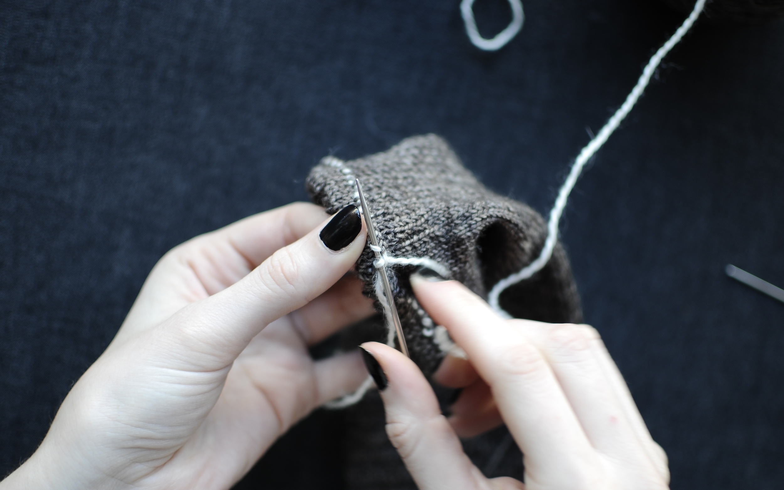 4. Insert knitting needle underneath Yarn B in the next section. Wrap yarn around needle again and knit that stitch.