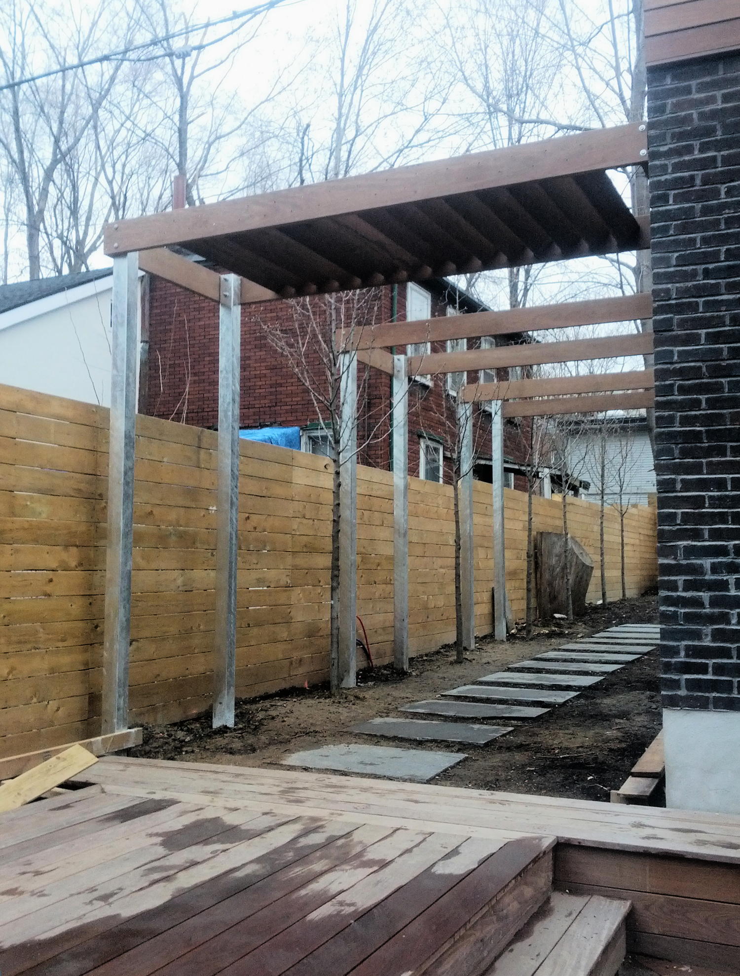 Modern arbors lining pathway to rear garden.