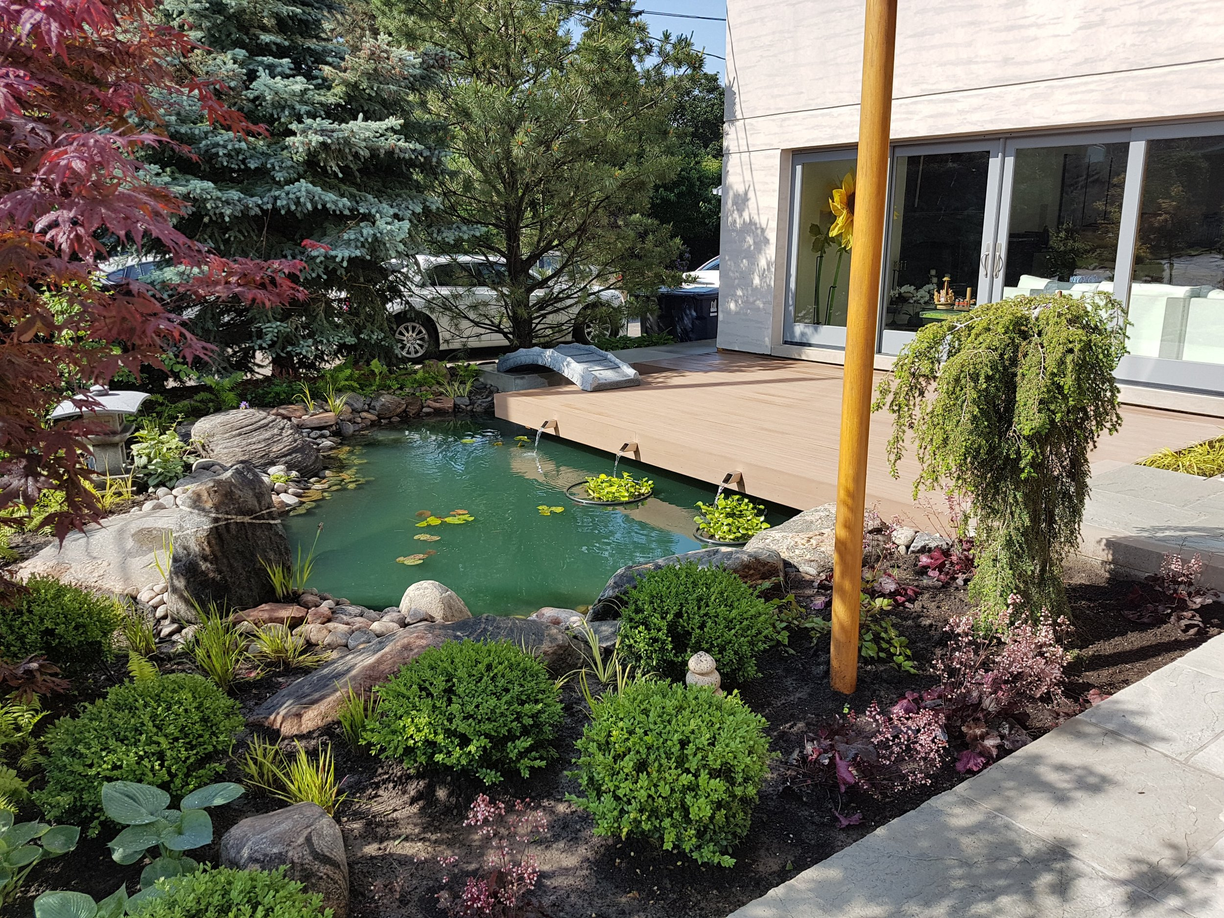 Upon walking futher into the space, you'll find a small and peaceful oasis that is protected from the business of the road. The soothing sounds of trickling water adds to the experience of the space, thanks to the simple water feature detail.