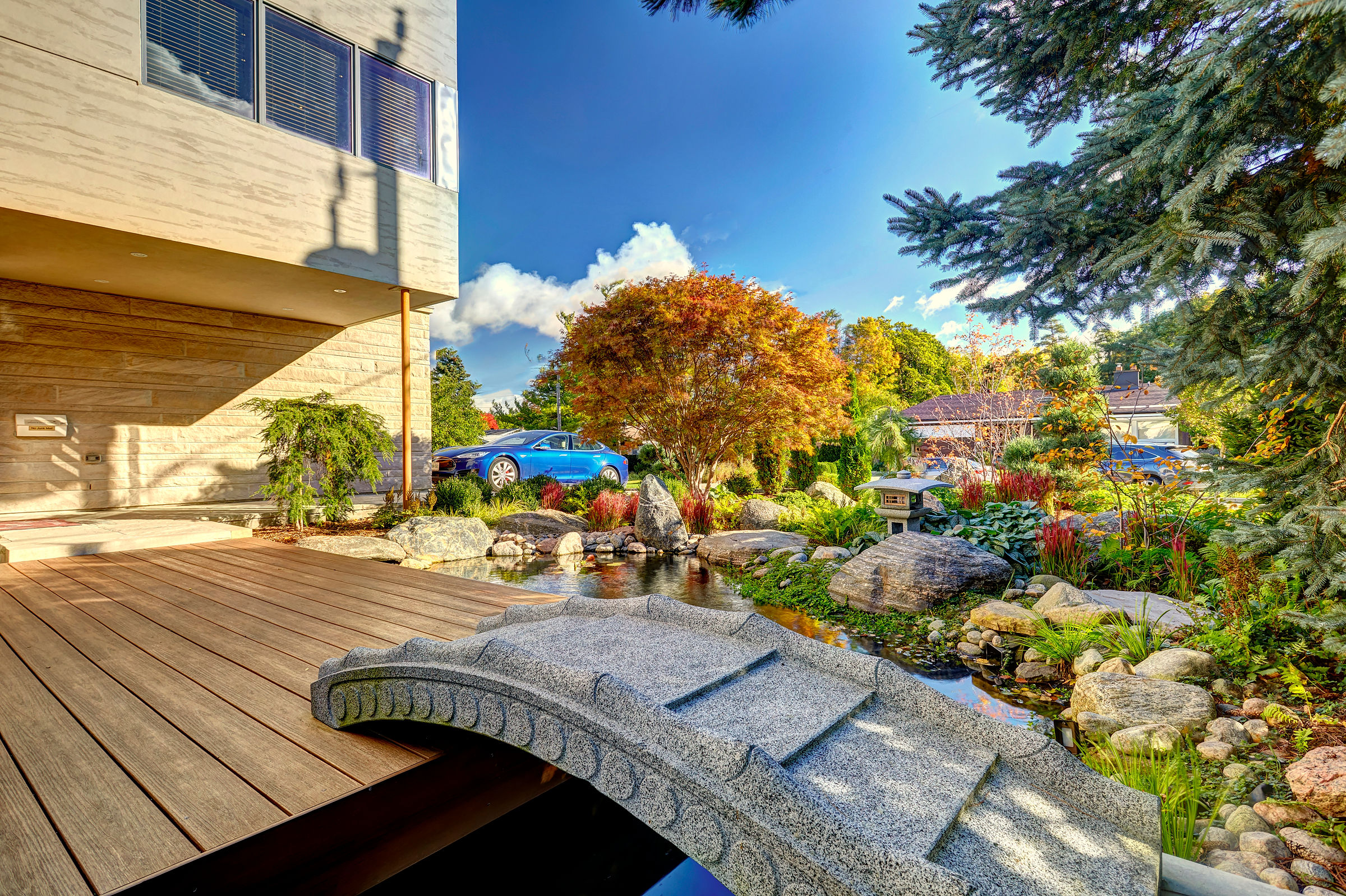 This small bridge is a great stylistic detail that completes the Japanese garden look, and also leads to back yard access.