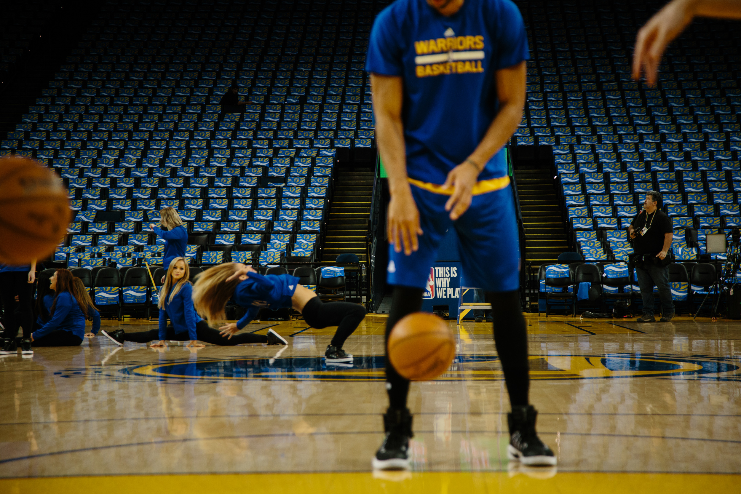McAdoo warms up before a Warriors home game. In the background, the Warriors dancers practice their dance routine. McAdoo is often the first one on the court warming up; he is so early that technicians are still finishing setting up pyrotechnics and dancers are rehearsing on the court at the same time.