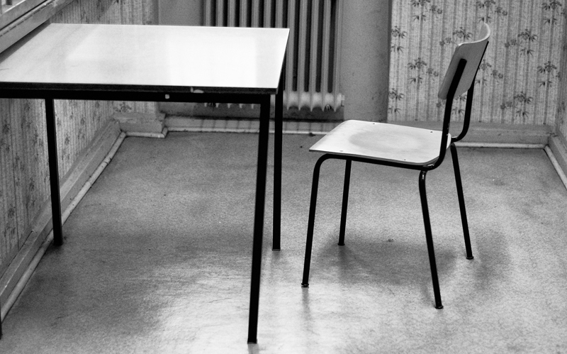 INTERROGATION   A lone chair sits in an interrogation room in the Stasi prison. More than 200 cells and interrogation rooms existed in the interrogation wing of the prison. Prisoners were isolated from the outside world, and expert interrogators subjected them to months of questioning.  The interrogators would coerce victims into making incriminating statements.