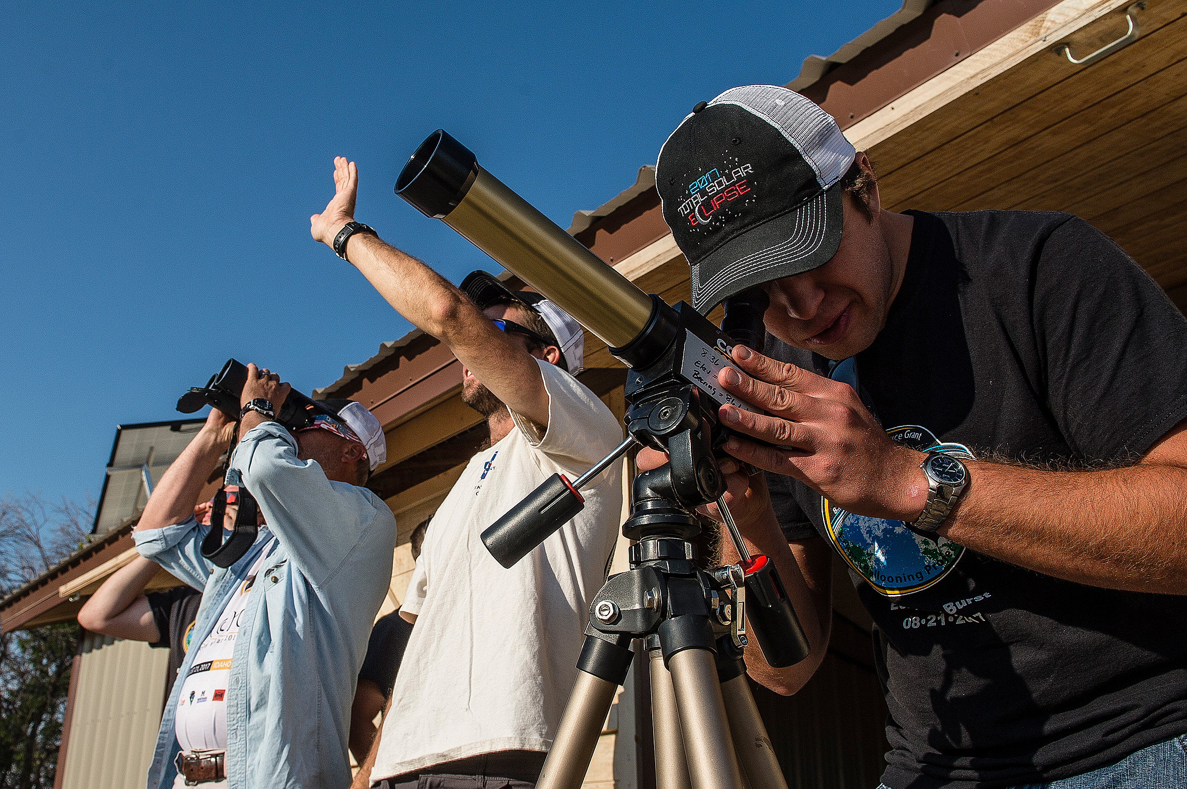 Members of MSU's balloon launch team watch the sun through solar scopes.