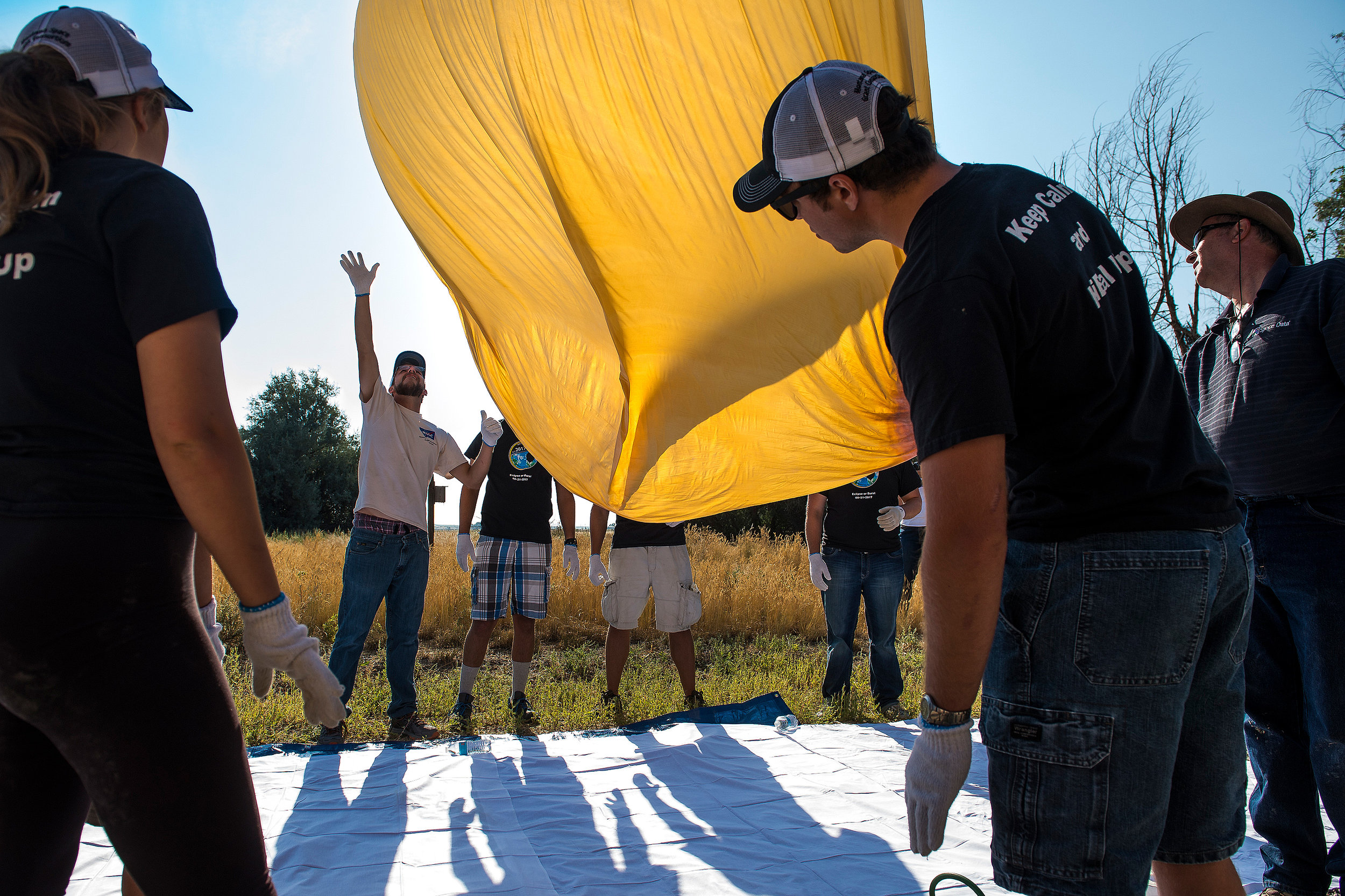 A latex balloon undulates and lifts off the ground as the MSU team fills it with helium. The team launched three balloons in roughly an hour before the eclipse so that cameras and other equipment they carried would reach the desired altitude during totality.