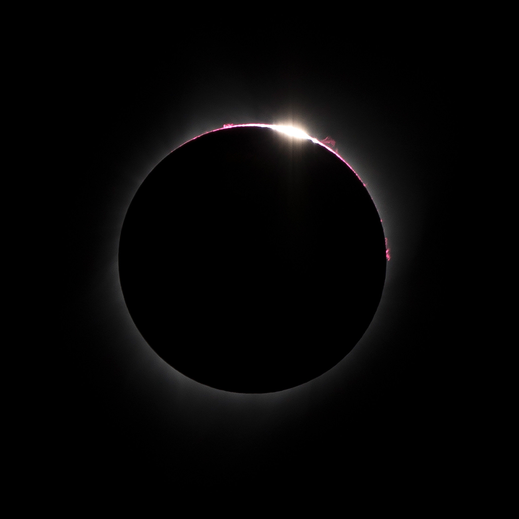 An image captured through a telephoto lens reveals solar eclipse features known as Bailey's Beads and the Diamond Ring effect.