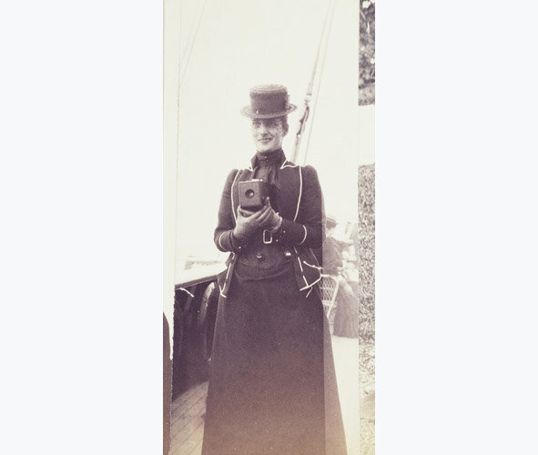 Image: Photograph of the Princess of Wales, later Queen Alexandra, holding a No.1 Kodak camera at chest height. She is standing on the deck of a ship.  The No.1 Kodak camera was introduced in 1889 and took small circular photographs. There are many examples of these photographs in Queen Alexandra's album  © Royal Collections Trust