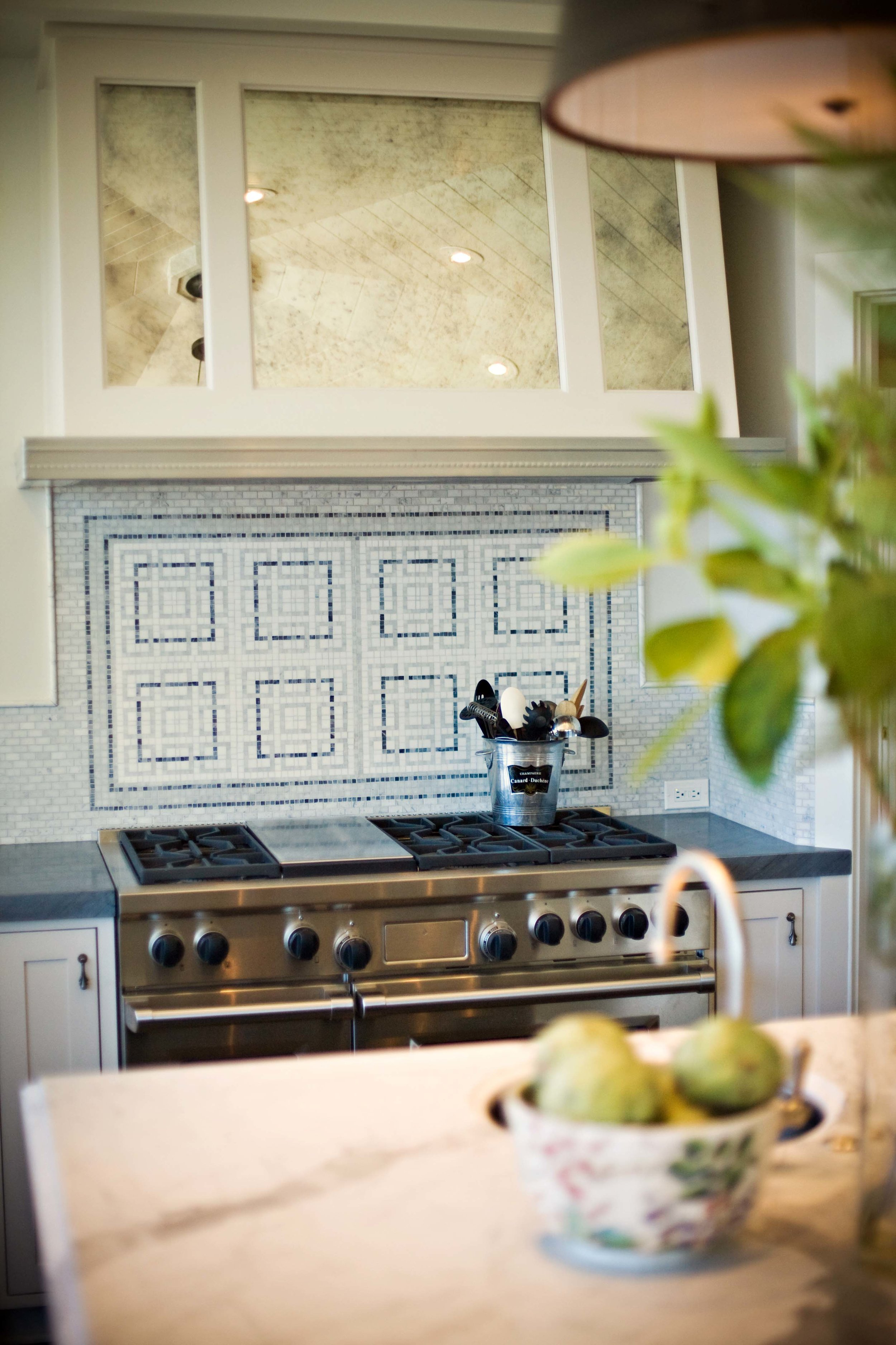 Details defined: This bespoke marble mosaic backsplash paired with the antique mirrored hood add interest.