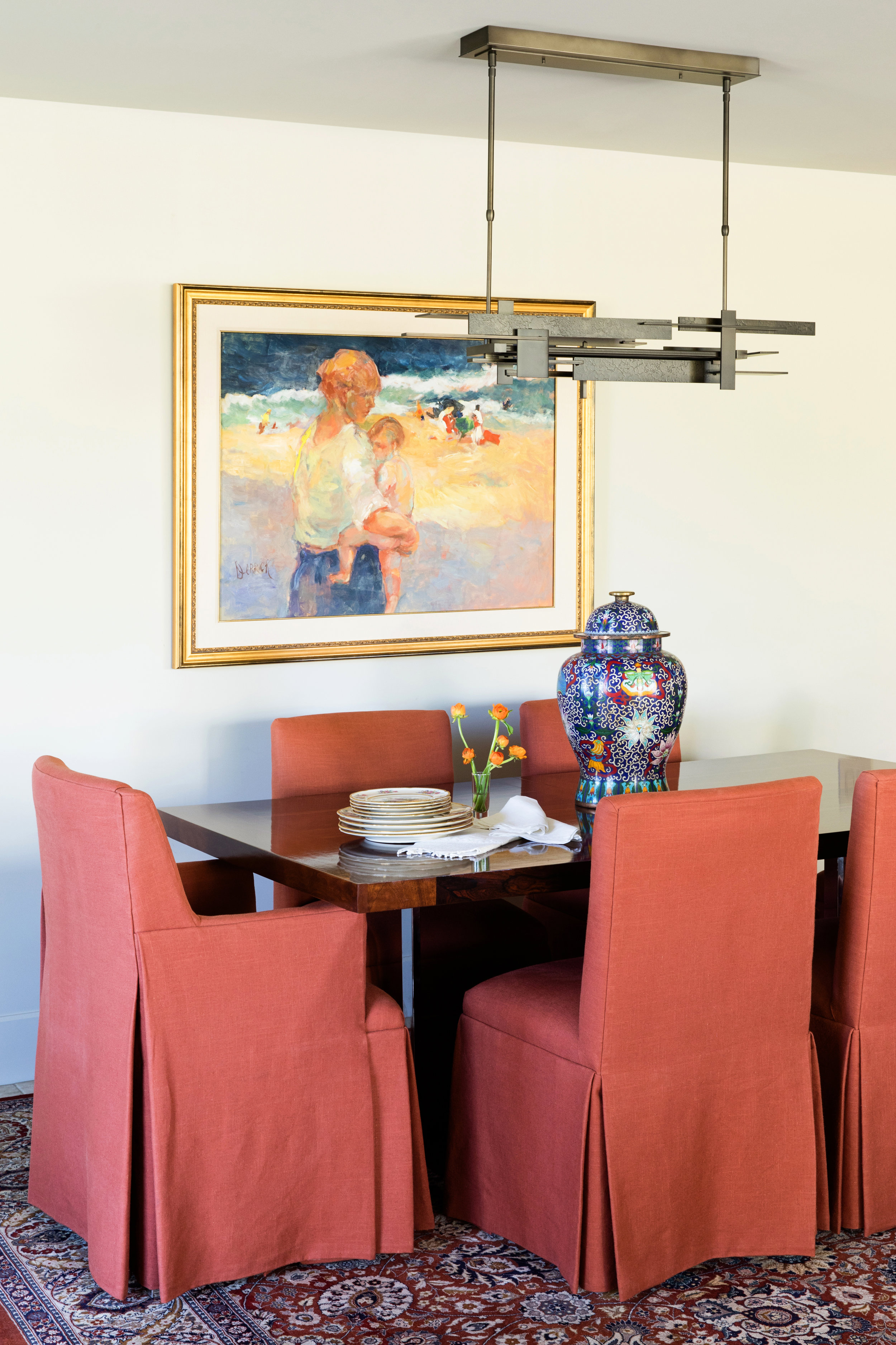 Traditional skirted chairs in persimmon skirts and a seaside painting by Sheryl Derrick bring color to the MCM rosewood dining table.