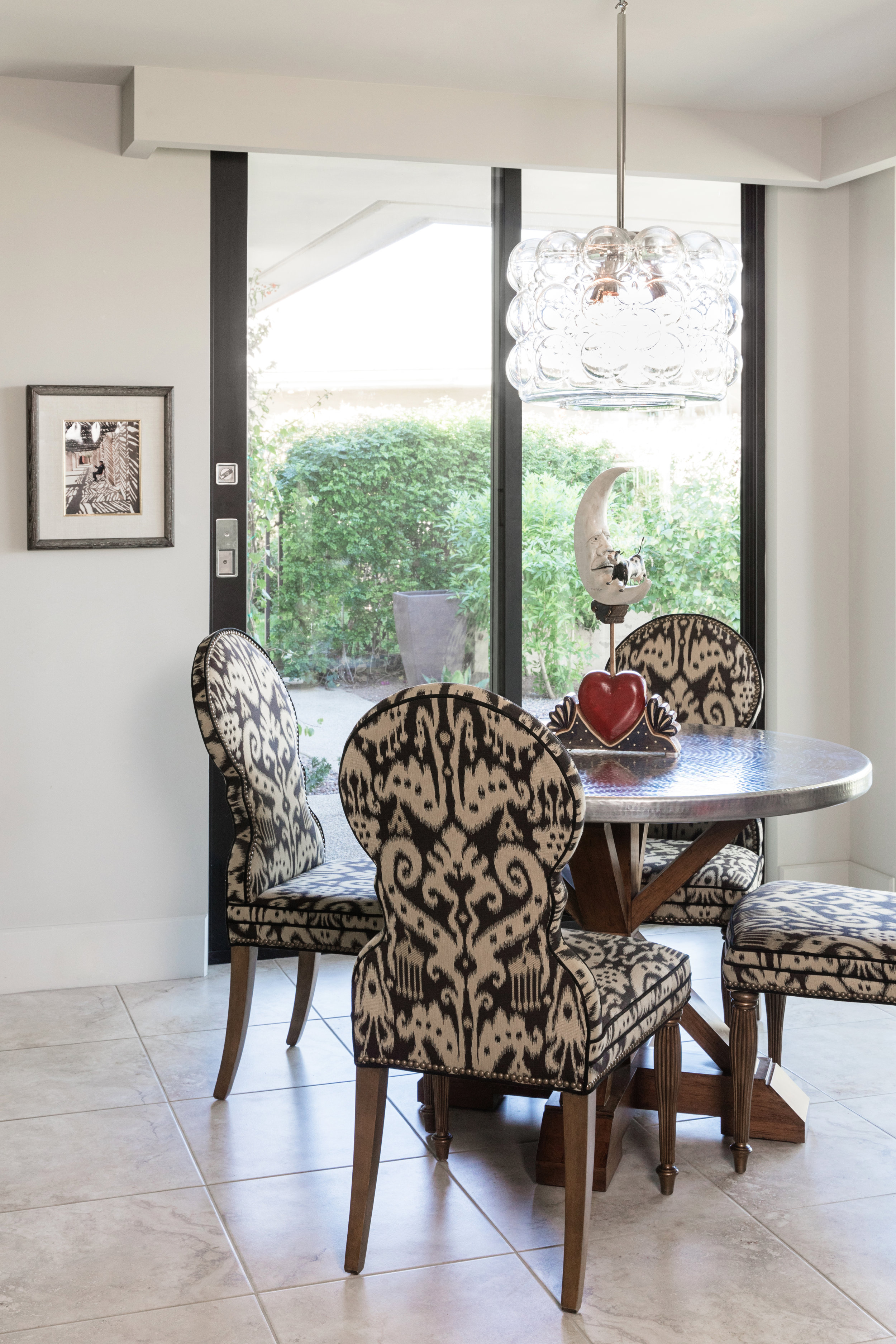 "Traditional chairs brought from the owner's Texas home find a place at the new metal-topped table in the ""Morning Room."""