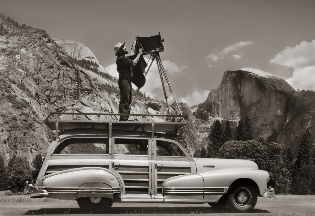 Ansel Adams, photographing in Yosemite National Park from atop his car about 1942. By Cedric Wright. Courtesy of the Cedric Wright Family