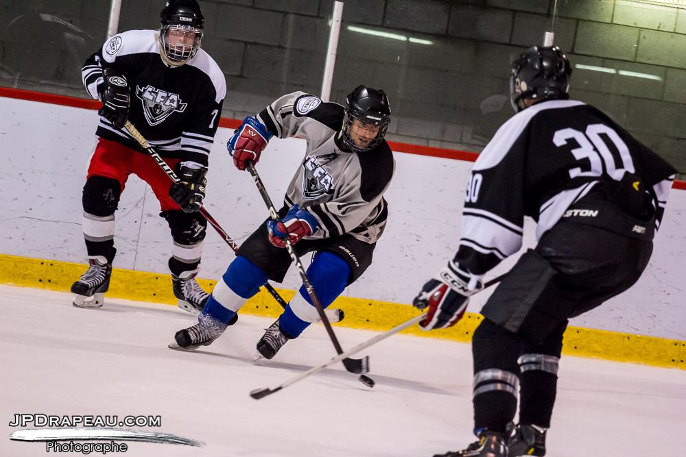The rookie, Benoit Des Roches from the Czechers,  swirling around against two opposing players from the Loggers.