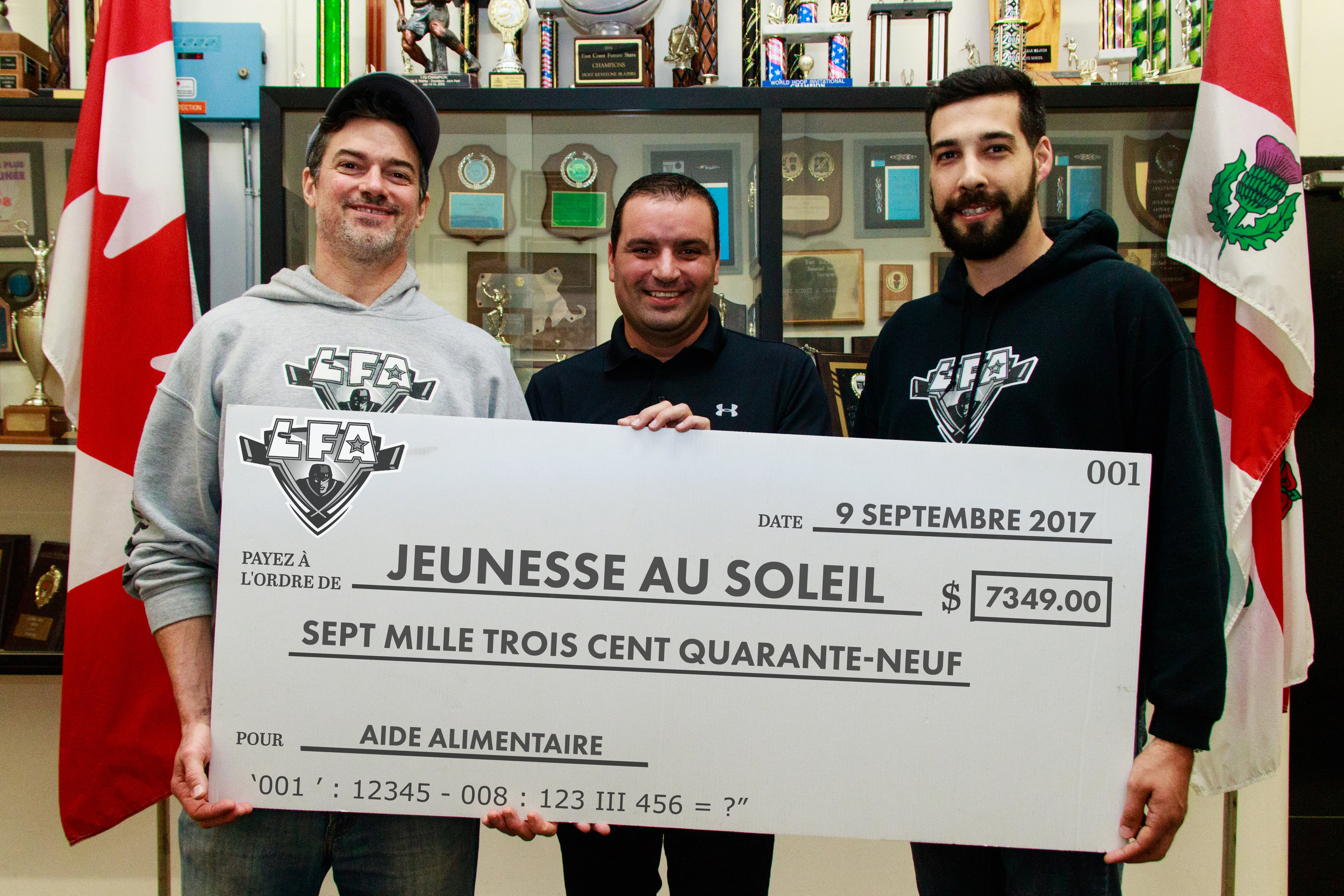MONEY RAISED FOR THE SUN YOUTH FOOD BANK DURING THE LFA'S SUMMER CHAMPIONSHIP GAME AUGUST 27TH (FROM LEFT TO RIGHT) THE CEO OF THE LFA JEAN-FRANCOIS DESBOIS WITH HEILO GALEGO FROM SUN YOUTH AND JACOB POLIQUIN THE DIRECTOR OF COMMUNICATIONS OF THE LEAGUE ,(PHOTO JOE FLEMINGS),