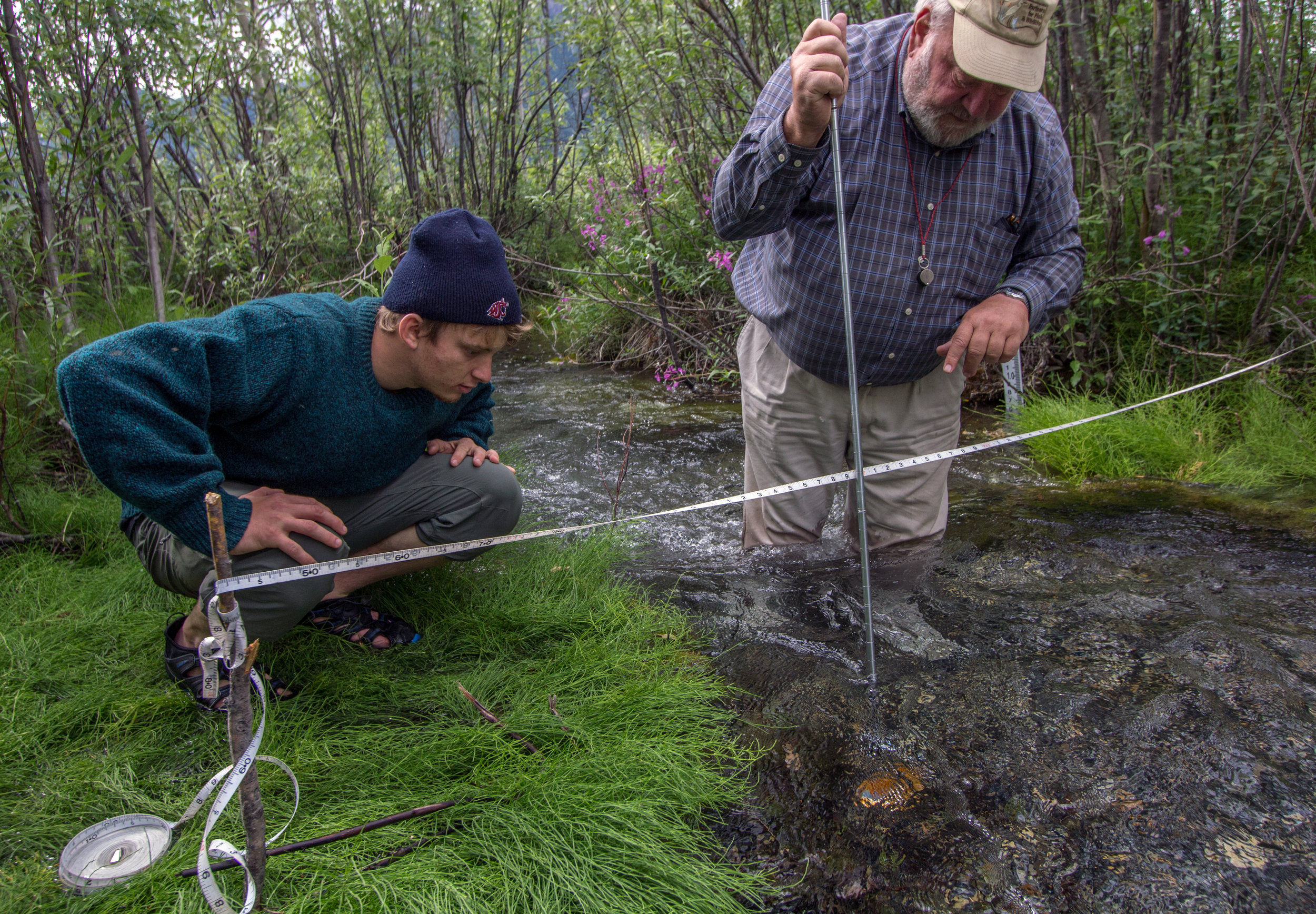A student and faculty member measure a stream cross-section.