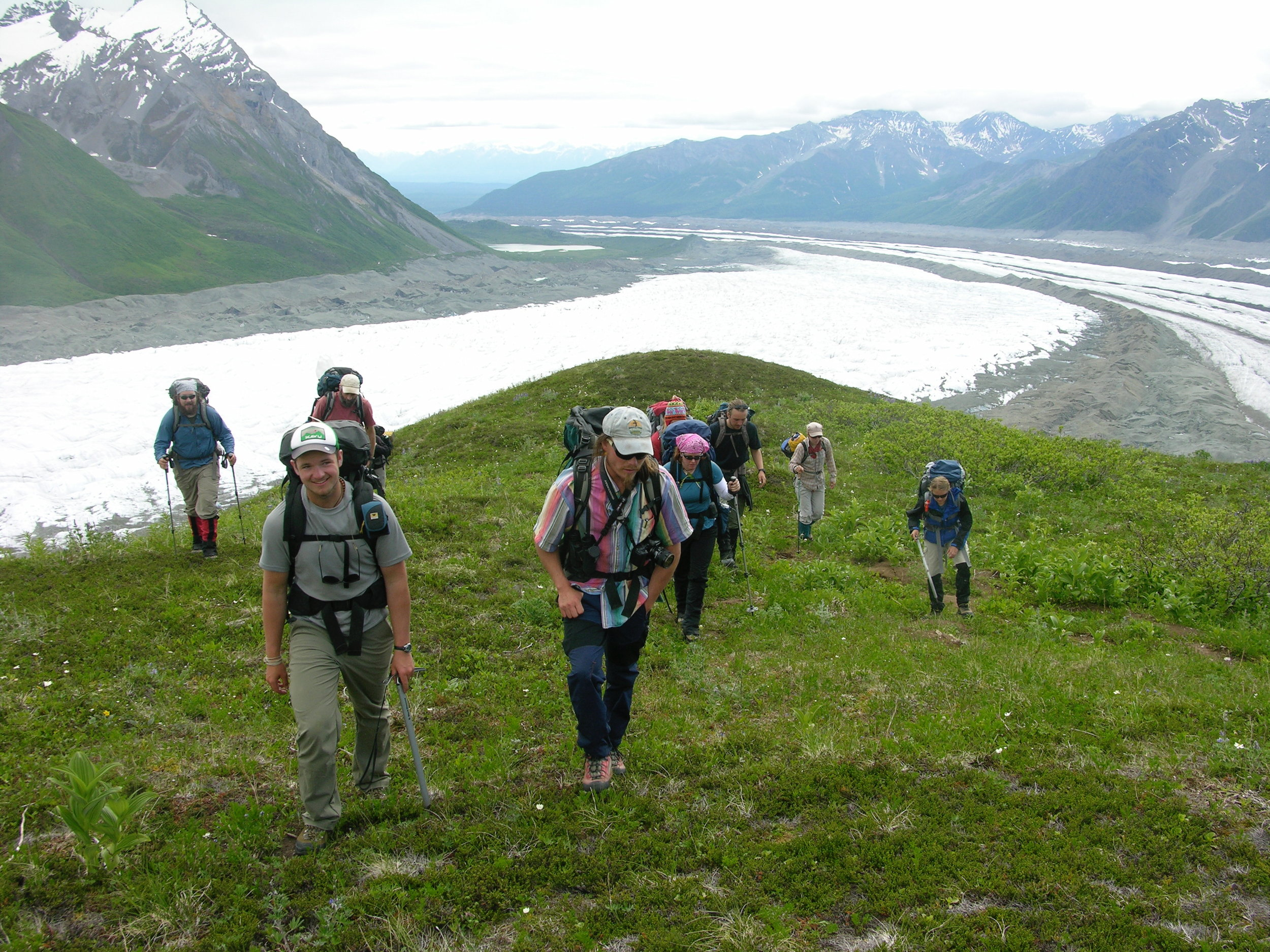 Students and faculty hike on an alpine ridge to a new campsite