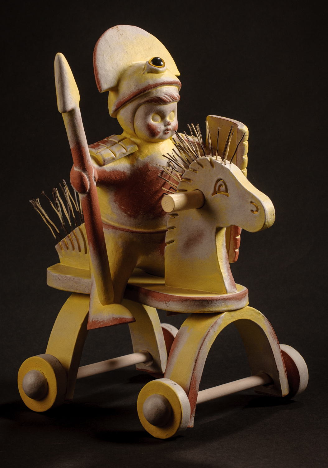 "Mounted Yellow Cyclopean Warrior, glazed & stained terra cotta, acrylic eye, broom straws, 13""h X 9""w X 12""d, 2011"