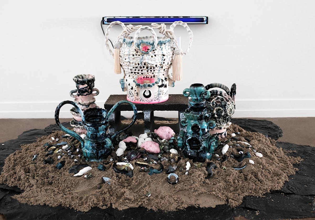 Zipporah Thompson, blue haze equinox, 2019, stoneware, oxides, glazes, wax, faux flowers, ribbon, foam, paint, sand, rubber mulch, cinder block, blacklight