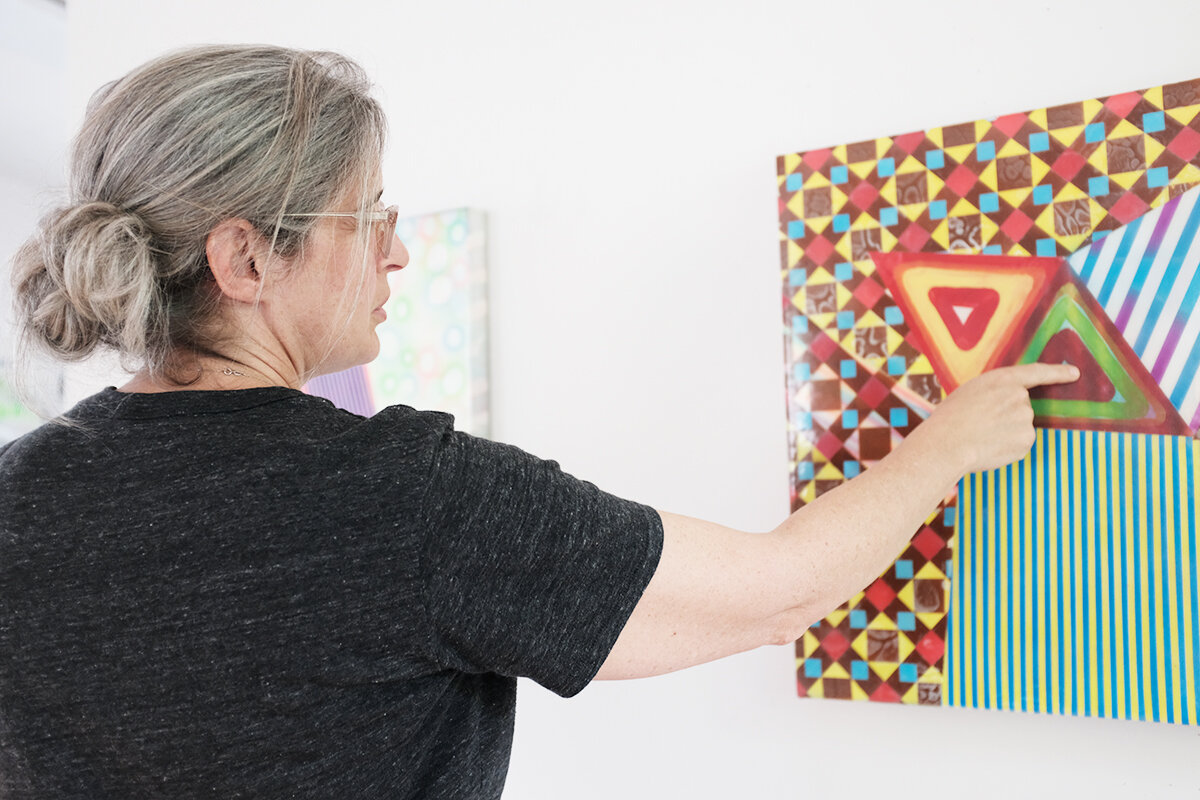 Alex Blau in her studio, points out a detail in her painting, Signal.